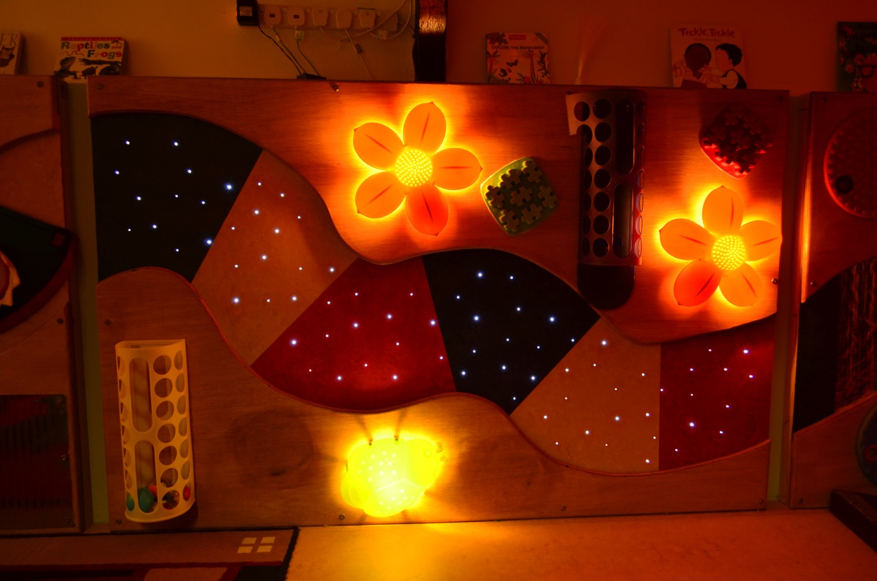 The Sensory Wall  The sensory wall stimulates the senses, where children can touch and feel the different textures; watch the twinkling stars, lighted flowers and bugs; look at their reflections in the mirrors; explore how things work by posting, sticking and tapping.