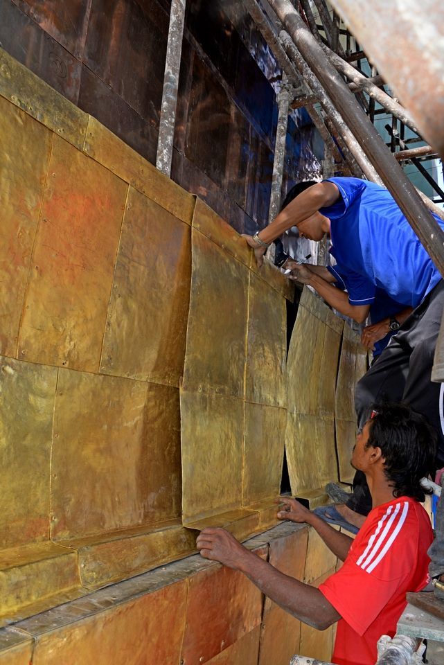 Gold plated panels being installed on the iron framework