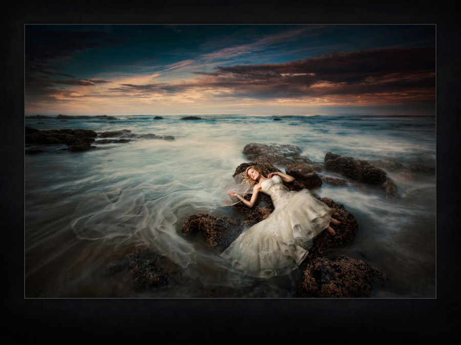 A Des Moines bride lays on a rock in the ocean and watches her veil wash back and forth in the tide. Destination wedding photographed in Oregon by Iowa Wedding Photographer of the Year McClanahan Studio. West coast wedding, dramatic sunrise portrait was selected for the 2014 PPA Loan Collection.