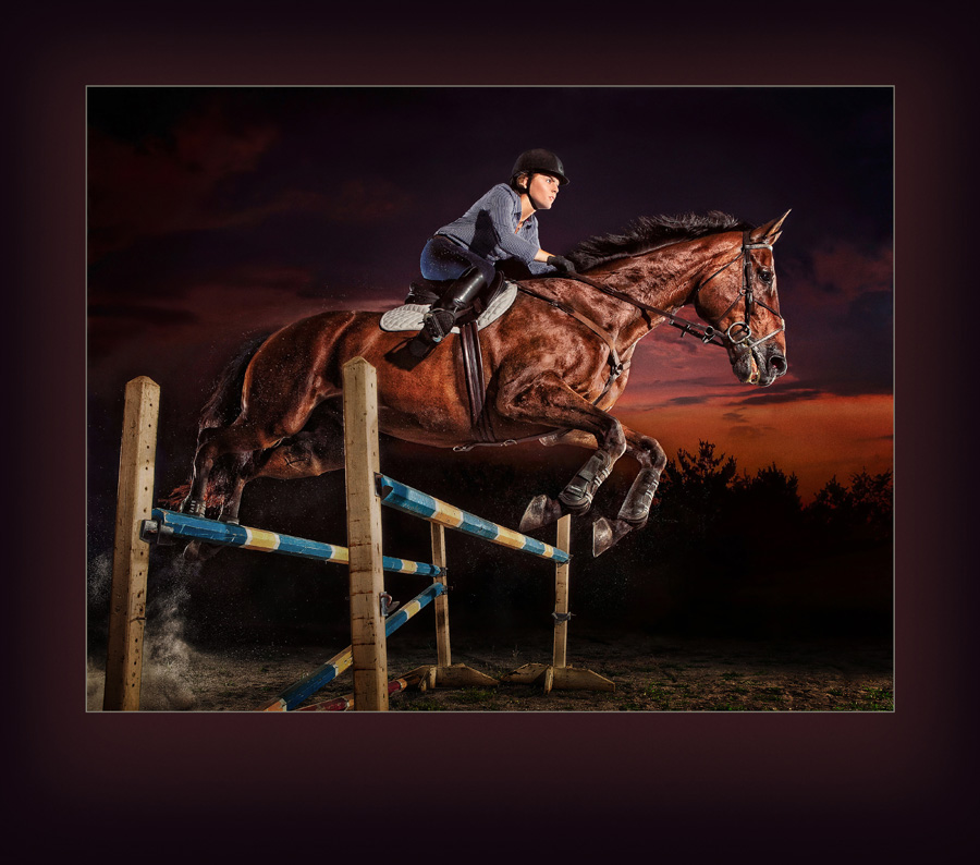 Ames high school senior Erin Lehman jumps her competition horse at dusk with a look of determination on her face. This strobist image accentuates the horse's muscles and shiny coat. Photographed in Ames, Iowa by Des Moines Photographer Dan McClanahan. Photo was selected for the 2014 PPA Loan Collection.