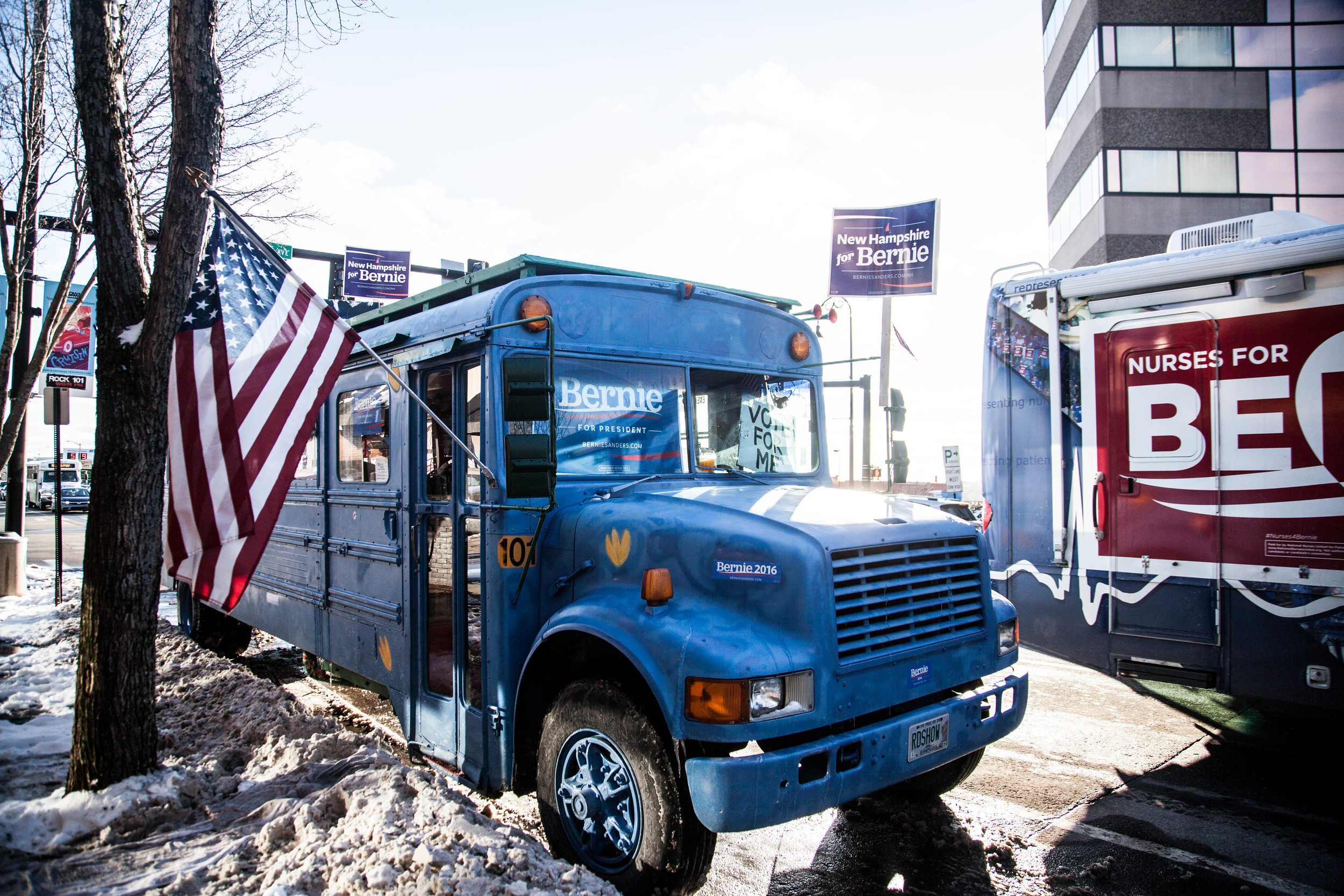 """Manchester, NH,Feb. 9, 2016 - A """"Nurses for Bernie Sanders"""" bus drives past another bus in support of Bernie Sanders parked on Elm Street. Photo by Alexandra Wimley"""