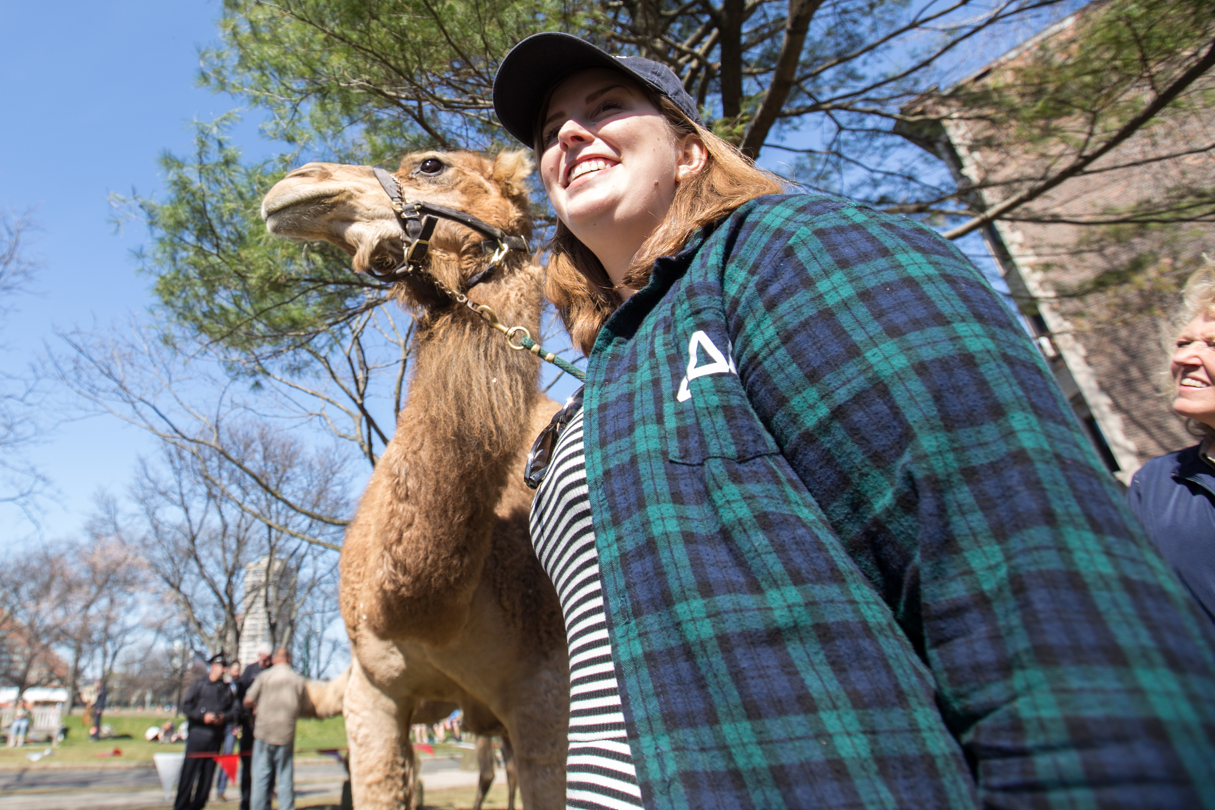 A students poses for a photo with a camel.