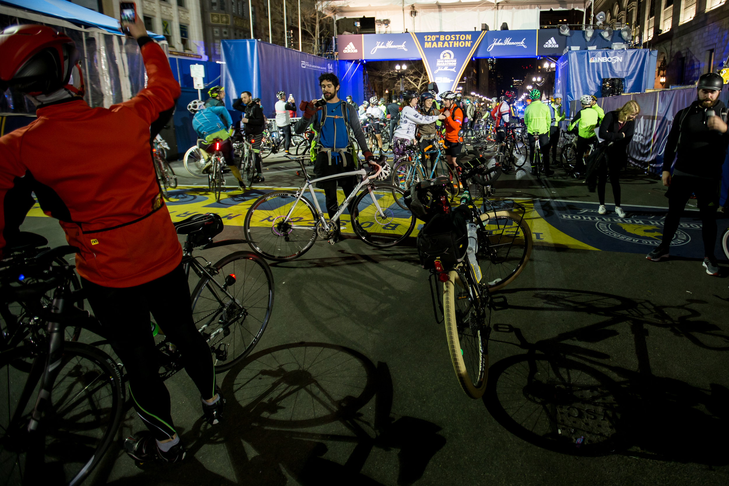 Participants rest and take photos after completing the Midnight Marathon Bike Ride, which begins at midnight on April 18 in Hopkington, Mass., and traverses the route of the Boston Marathon.