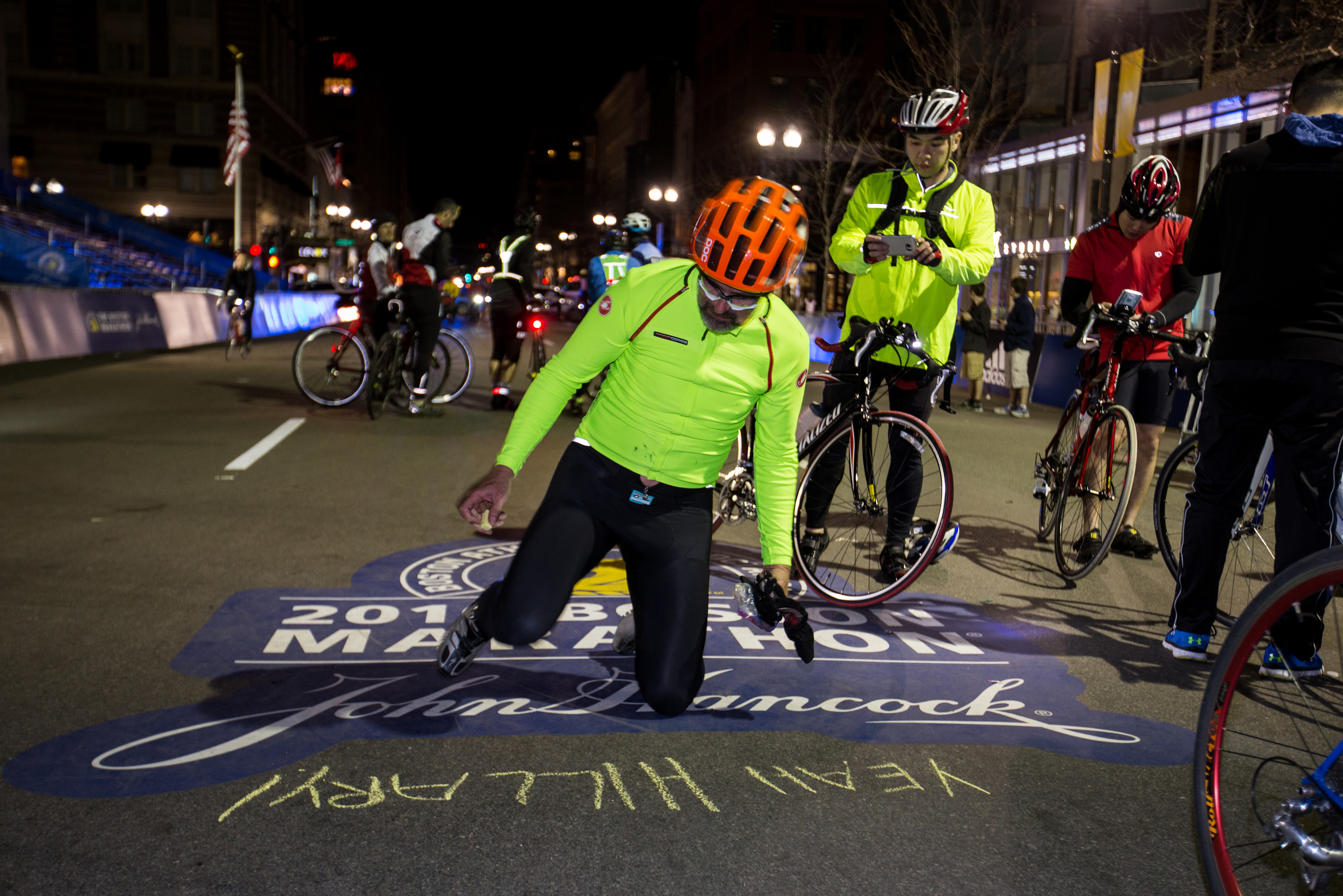Vincent Chahley writes words of encouragement to his friend Hillary, who ran the marathon the next day, after completing the Midnight Marathon Bike Ride, which begins at midnight on April 18 in Hopkington, Mass., and traverses the route of the Boston Marathon.