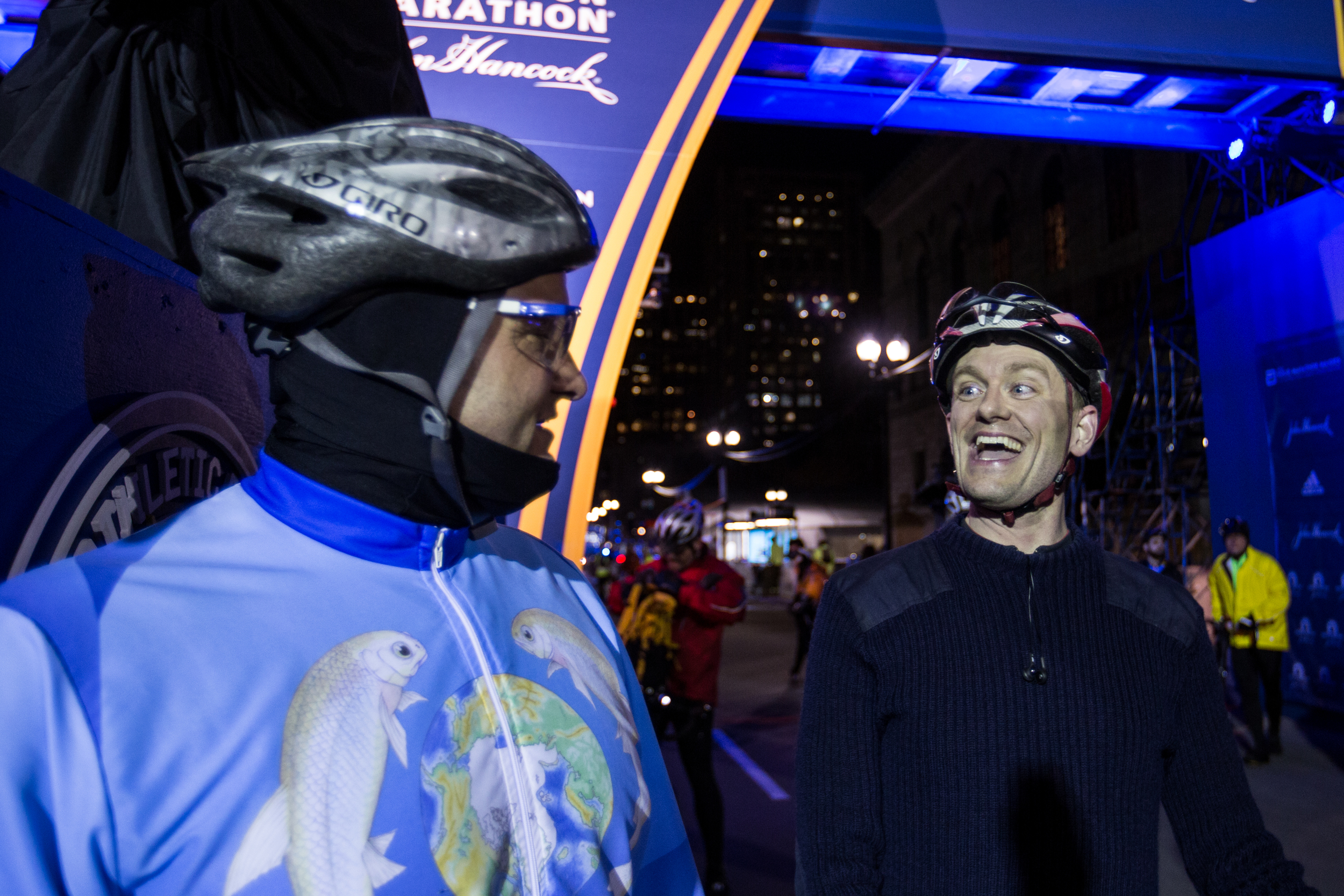 (From left) Ulysses Sallum and David Haines laugh after completing the Midnight Marathon Bike Ride, which begins at midnight on April 18 in Hopkington, Mass., and traverses the route of the Boston Marathon.