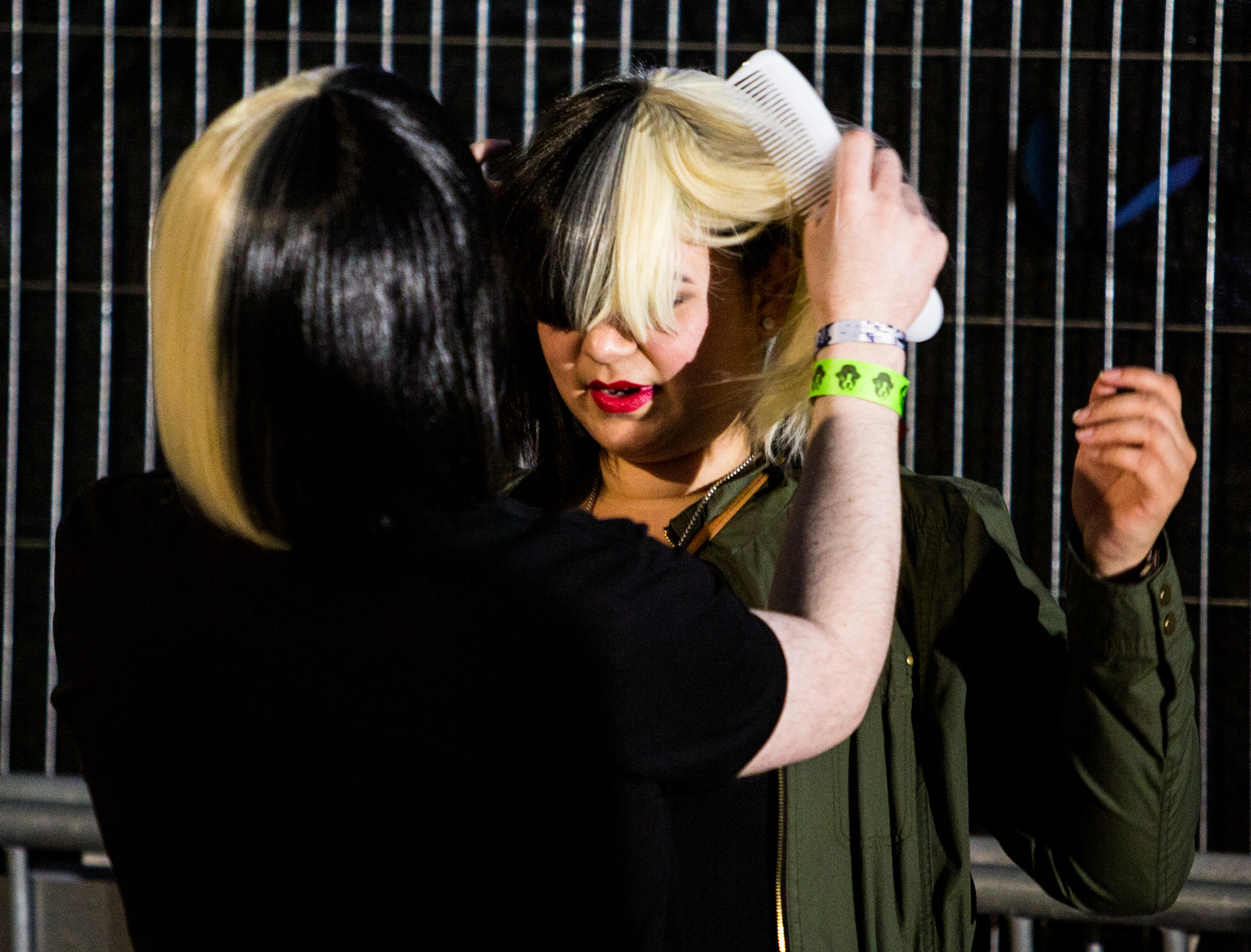 Two Sia fans adjust their wigs before her performance.