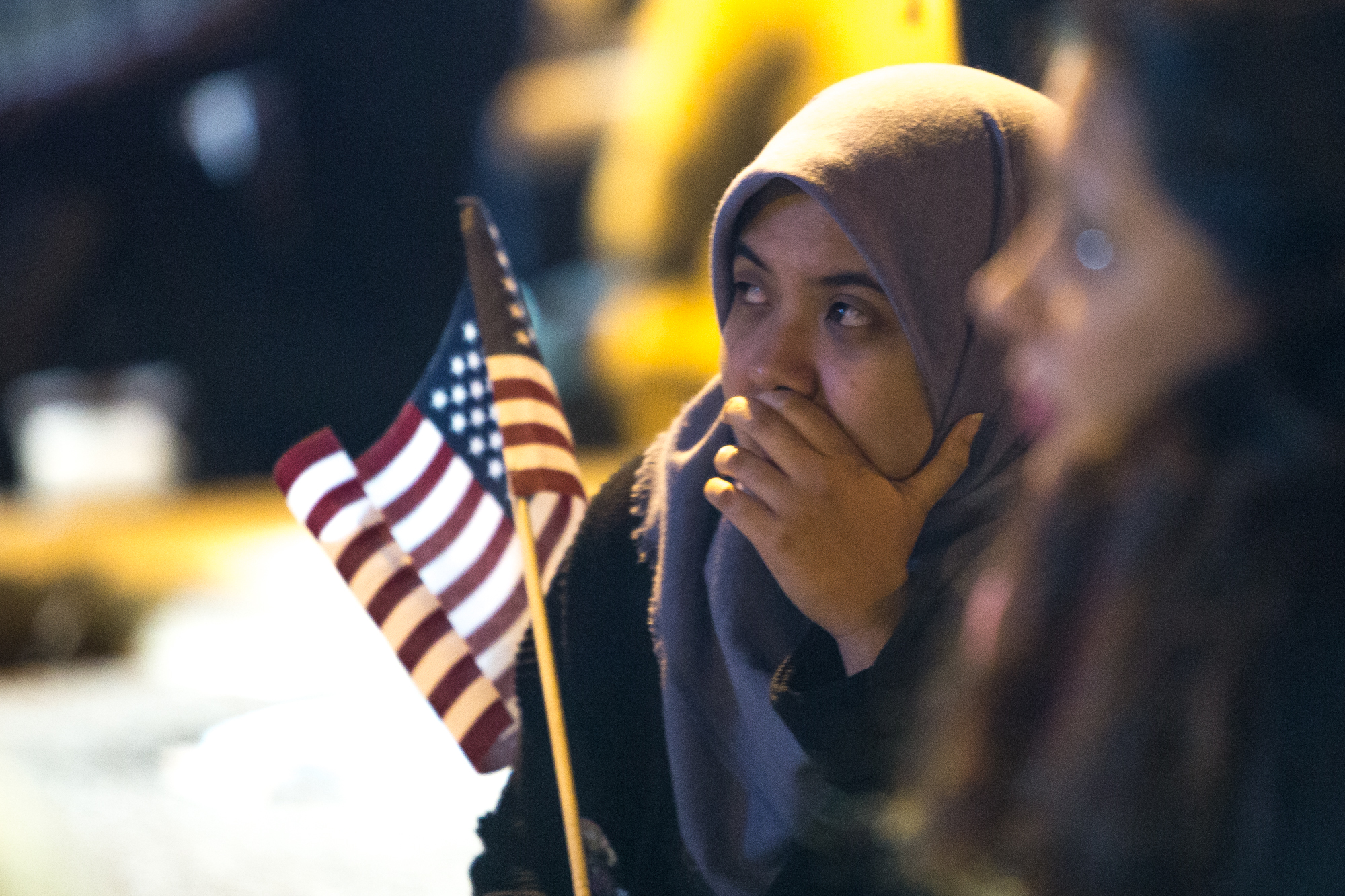Farah Amalia, 21, of New York, watches commentary on the big screen television late in the night outside the Jacob K. Javits Convention Center in the early hours of Nov. 9, 2016. Earlier in the night, the venue was packed with room for standing only, but at attendees trickled out people began sitting on the ground or on the fence enclosing it. Some attendees had been waiting in line since about 1 p.m.
