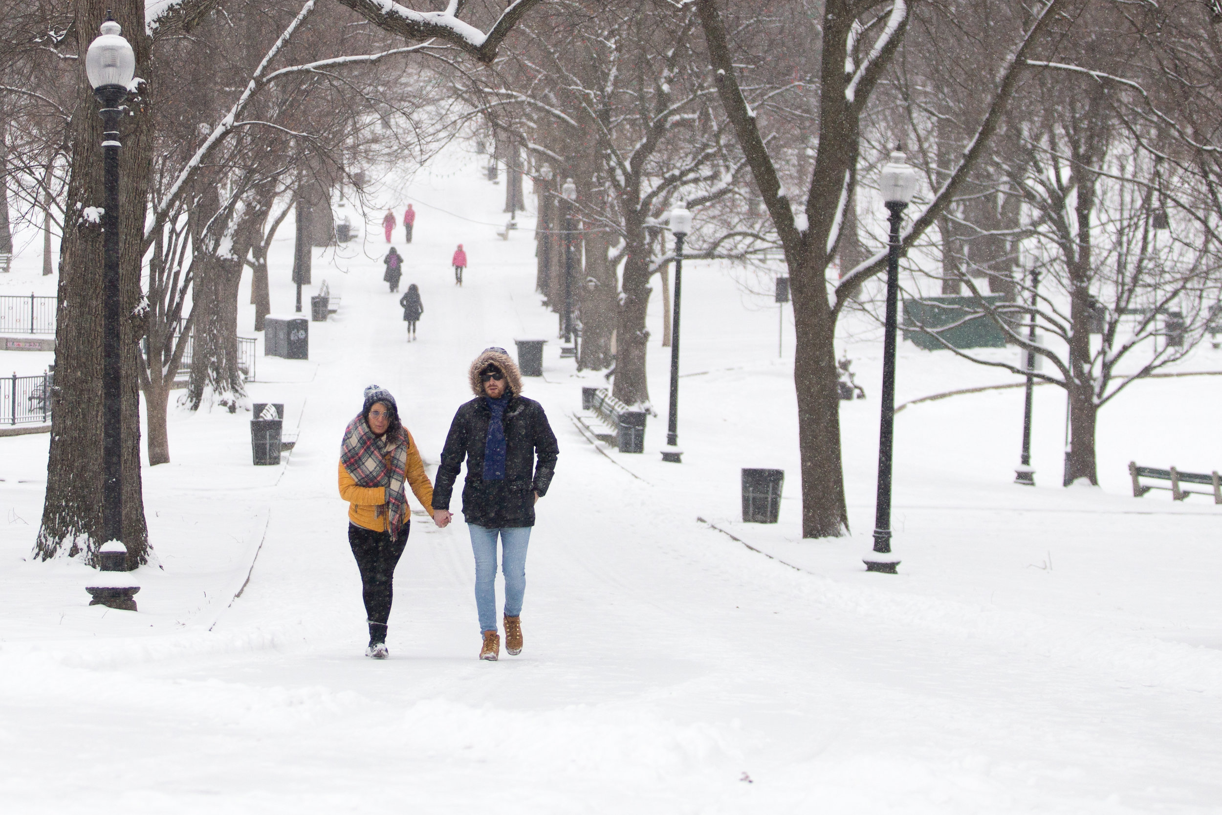 People brave cold and snowy weather to walk in the Boston Common Dec. 17, 2016.