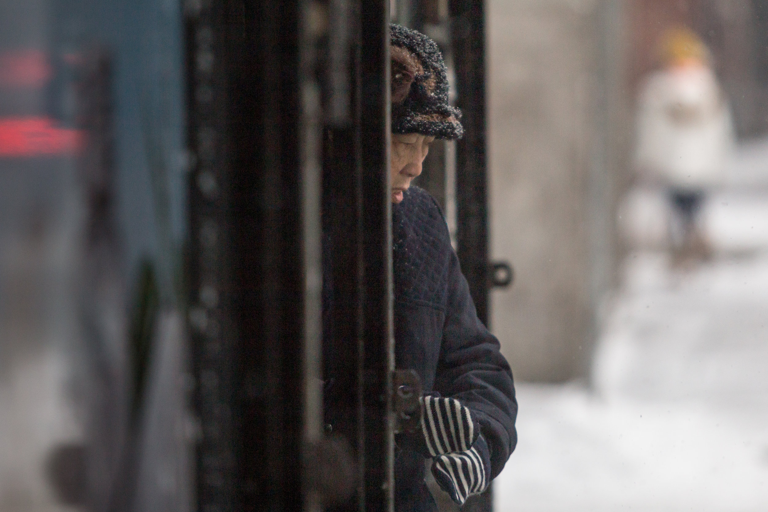 A woman takes refuge from the snow under an awning in Boston's Chinatown Dec. 17, 2016