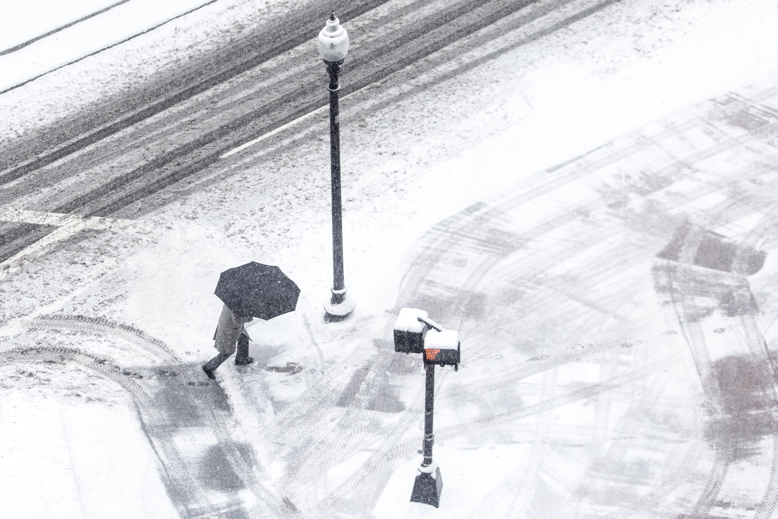 A man shields himself from the snow with an umbrella while crossing a street in the North End of Boston on Dec. 17, 2016.