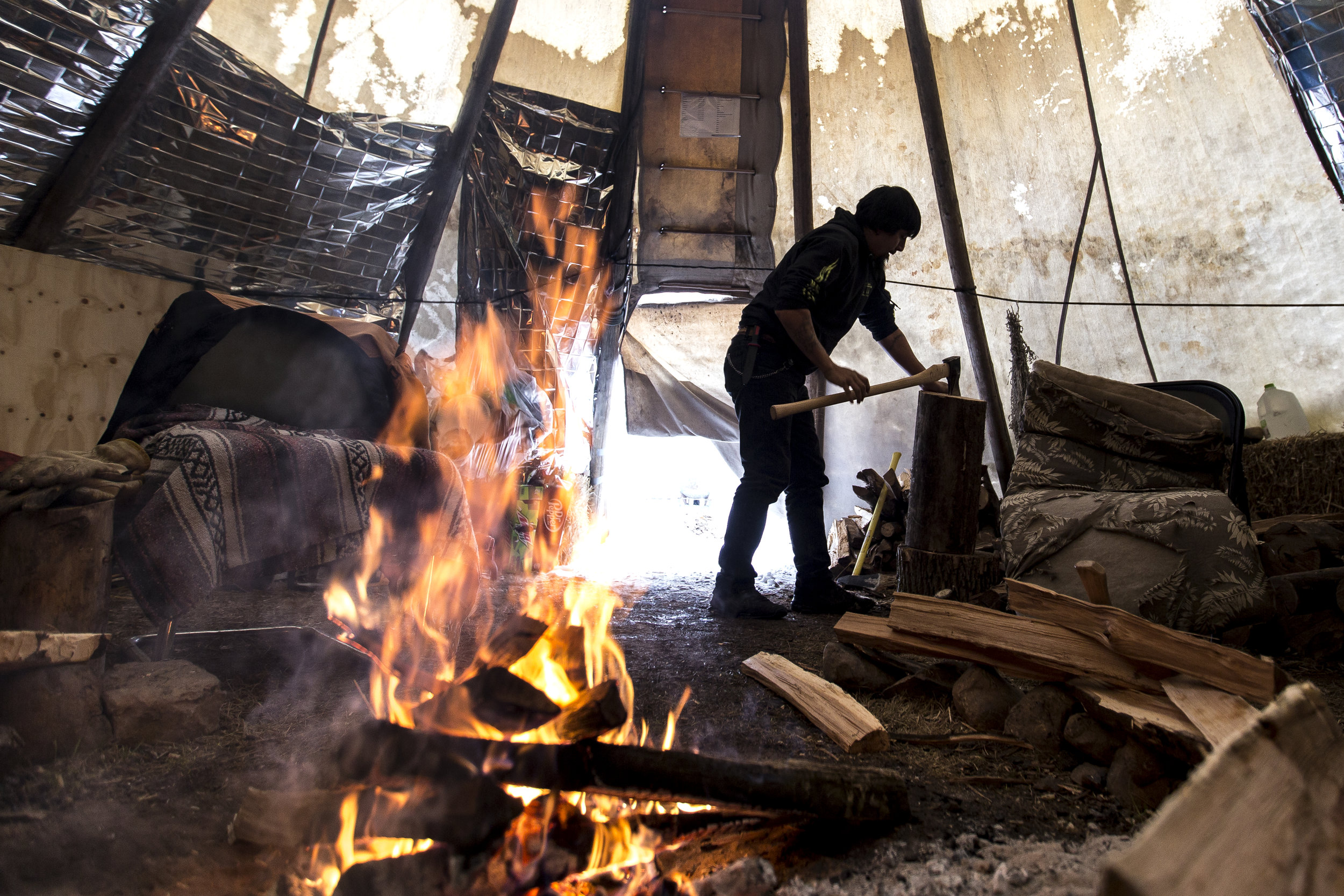 Frank Vandehei chops wood for the fire inside the teepee in Oneida, Wis., Wednesday, December 13, 2017.