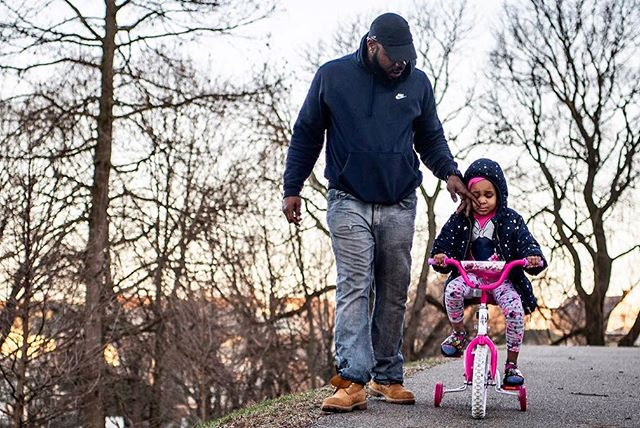 """She's a little nervous. Up the hill is ok, but downhill's a little scarier."" Jamar Reese of Crafton wipes away a tear for his daughter Giaonia, 5, after she got frustrated learning to ride a bike for the very first time this evening at Emerald View Park. (Alexandra Wimley/Post-Gazette)"