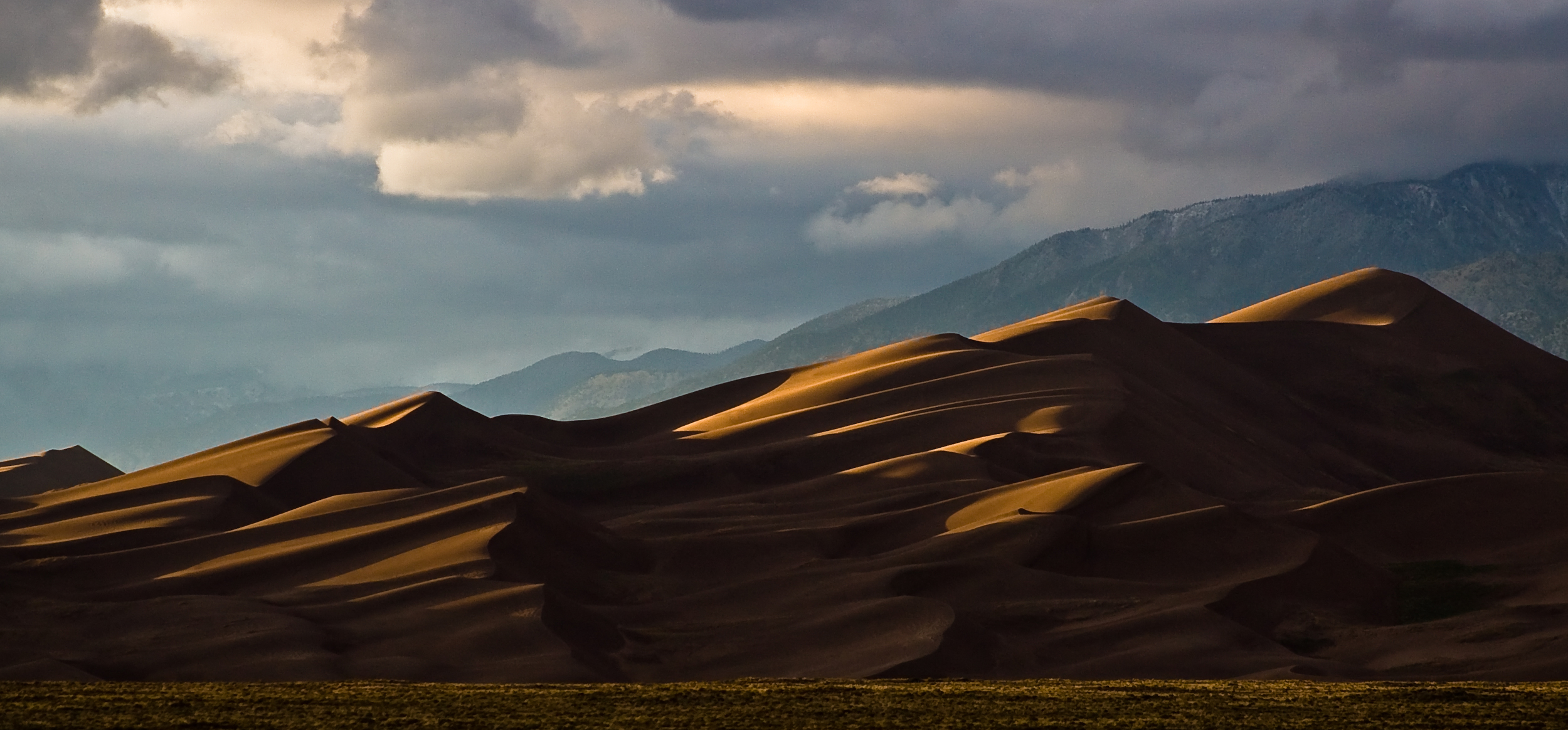 The dunes were formed from sand deposits of the Rio Grande and its tributaries, flowing through the San Luis Valley. Over the ages, westerly winds picked up sand particles from the river flood plain. As the wind lost power before crossing the Sangre de Cristo Range, the sand was deposited on the east edge of the valley. This process continues, and the dunes are slowly growing. The wind changes the shape of the dunes daily.