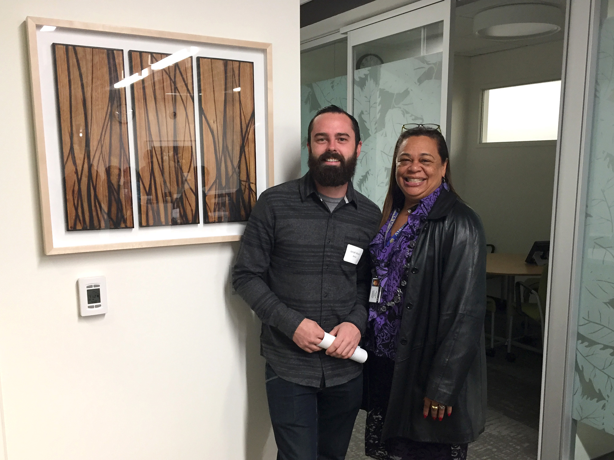 Jonah Ward with Edna Boatwright, an Artwork Selection Committee Member, standing next to one of his glass burned panels selected for the building.