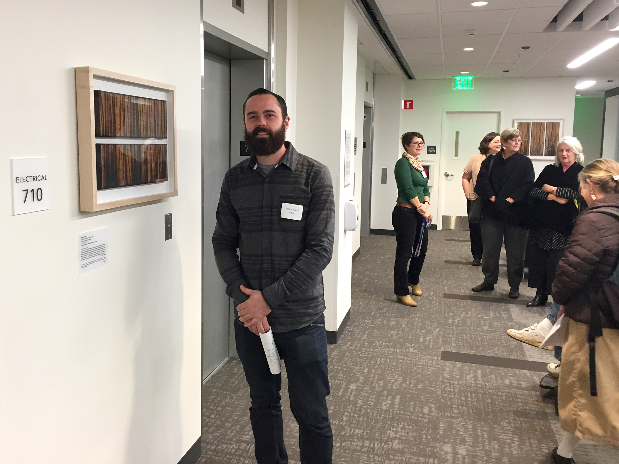 Jonah Ward stands next to another one of his permanently installed glass burned panel pieces during the artist walk-through. The other piece can be seen in the back right.