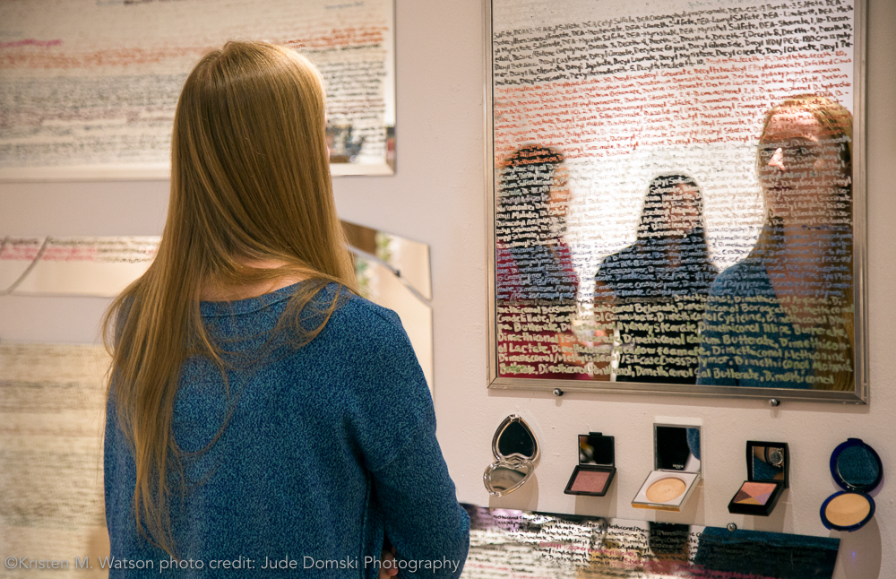 """Visitor interacting with  rəˈflekt , kristen m. watson,2016, cosmetics ingredients list written using make up on mirror, overall dimensions approximately 60"""" x 240"""". written alphabetically by mirror from left to right."""