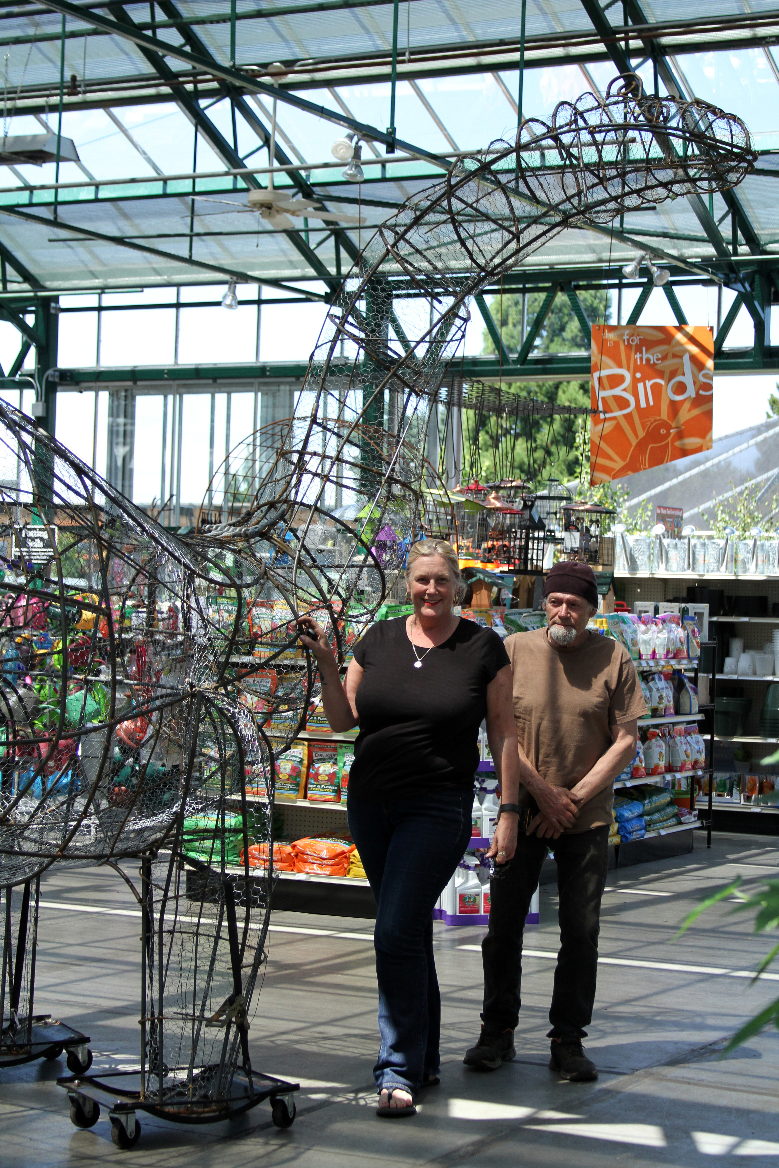 The artist and a member of her assembly team standing near the newly-installed sculpture
