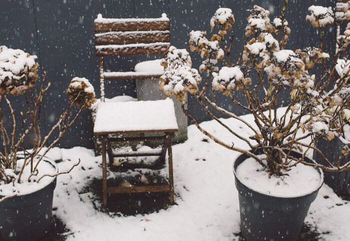 high-angle-view-of-snow-covered-chairs-and-potted-plants_700x483.jpg