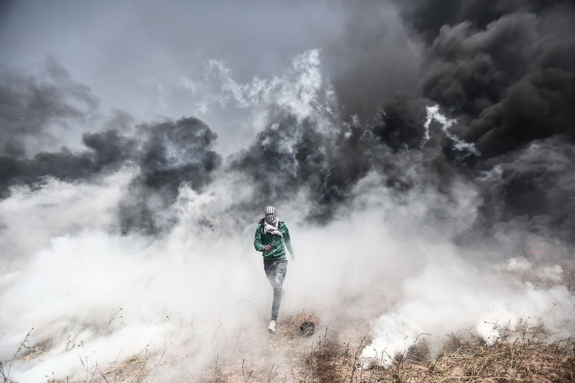 KHAN YUNIS, GAZA - APRIL 6: A Palestinian demonstrator escapes heavy smoke as Israeli soldiers fire several gas bombs during his participation in the 'Great March of Return,' despite Israel's threats near the Gaza-Israel border in Khan Yunis, Gaza on April 06, 2018. Demonstration against Israel's blockade of the Gaza Strip started taking place 11 years ago. Mustafa Hassona/Anadolu Agency