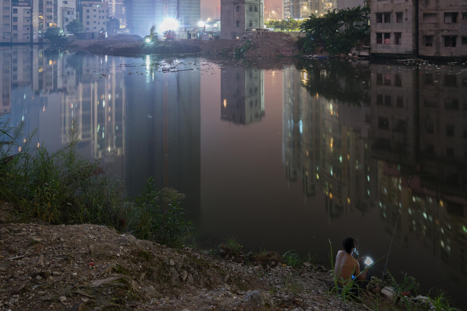 A lone migrant worker playing with his mobile device. Tong Lam