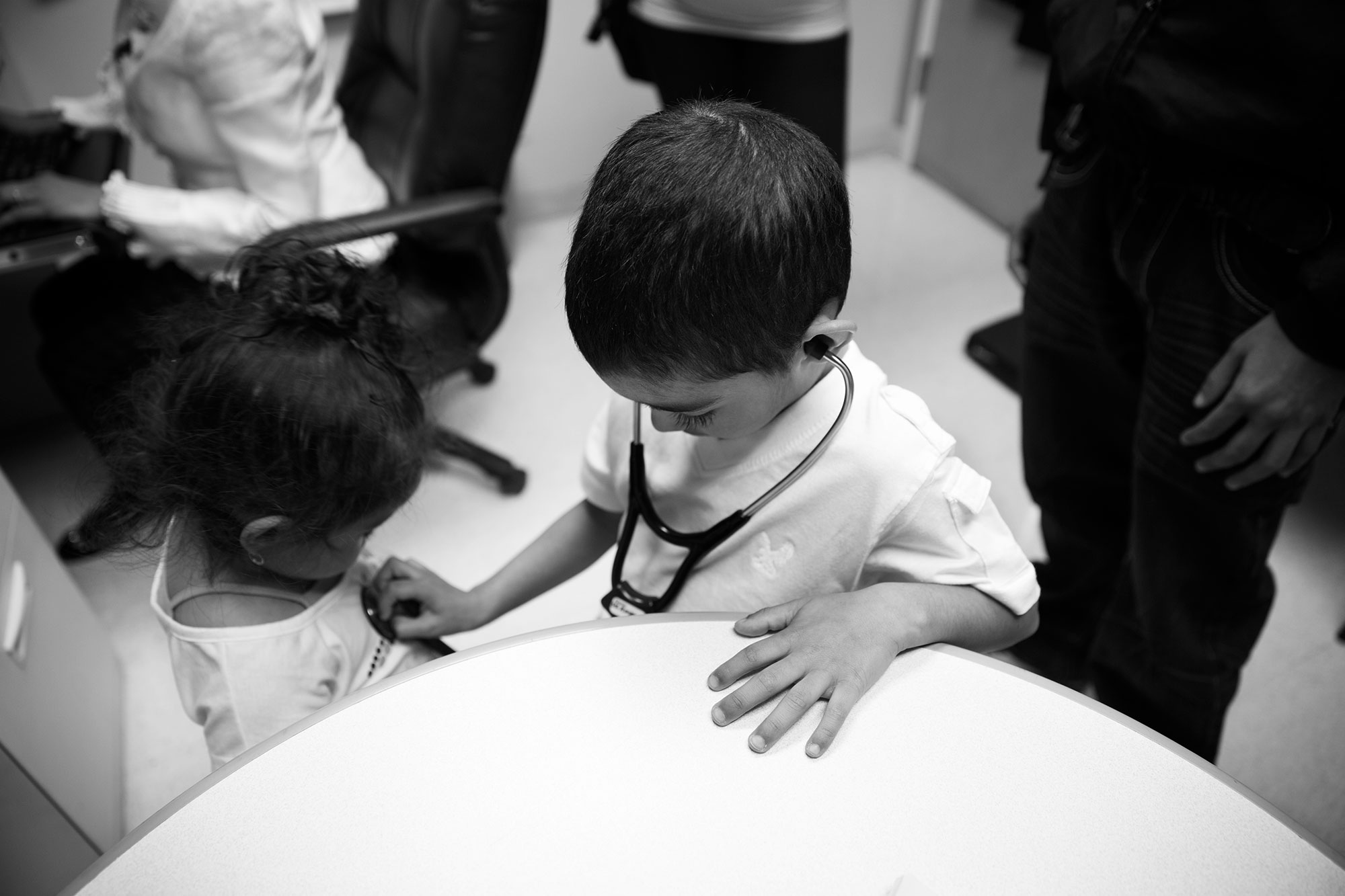 Kelvin uses a stethoscope on his sister.