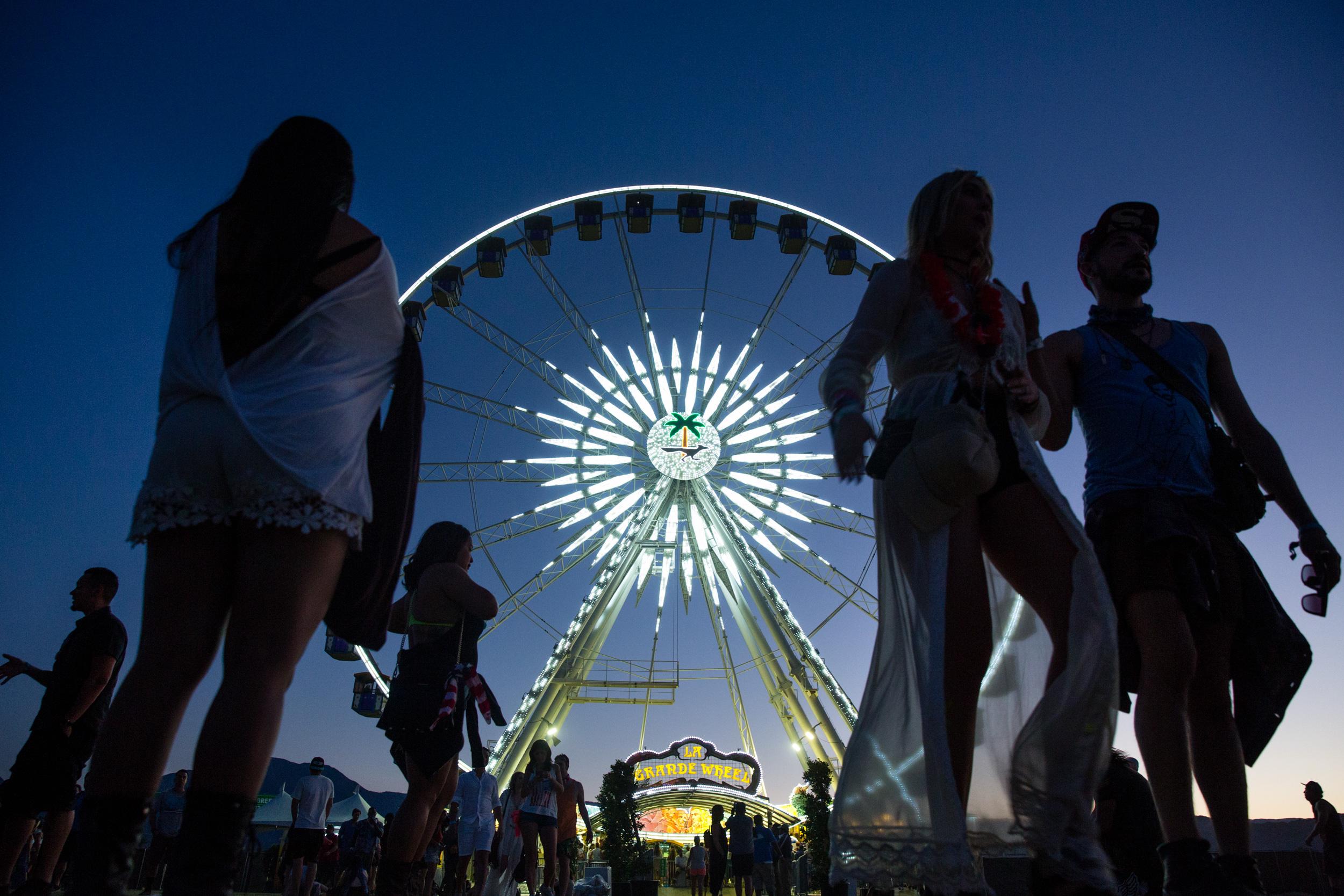 Attendees walk past the Coachella Ferris wheel at the festival entrance.