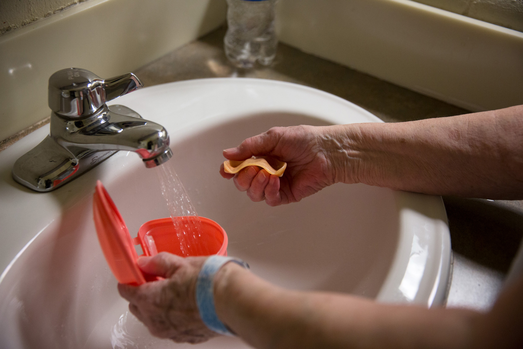 Norma, 76 years old, cleans her teeth after breakfast at Maine Correctional Center.