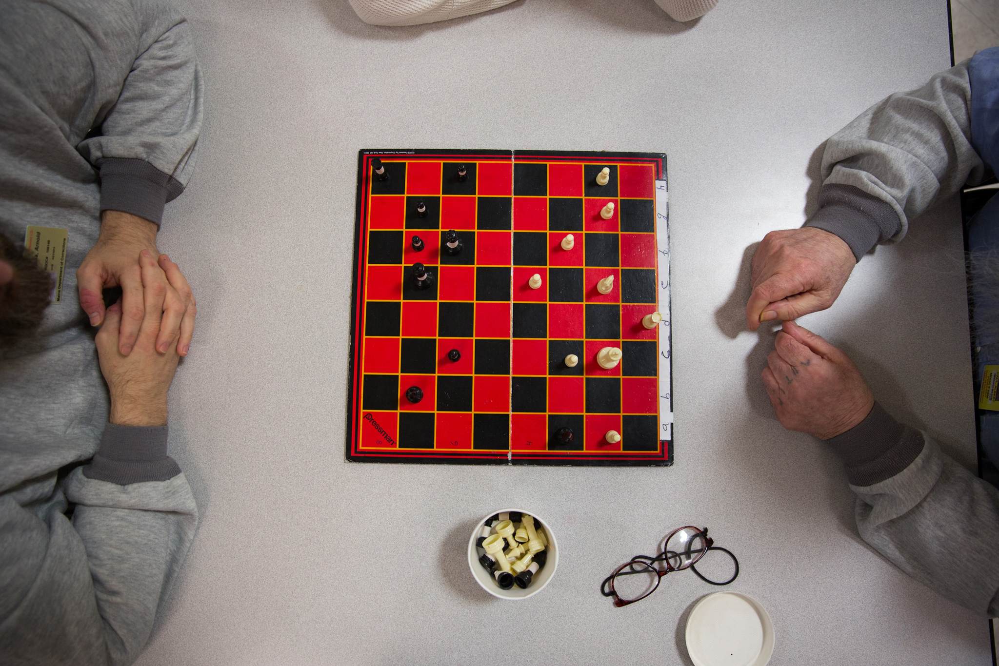 "Albert (right), 82 years old, plays chess with another inmate. Albert, who is wheelchair bound, rarely travels farther than 30 feet from his cell. When he does ""travel"" he plays chess (8 ft away), boils water for tea (30 ft away), or picks up one of his three meals from the guard desk (15 ft away) which he eats in his cell."