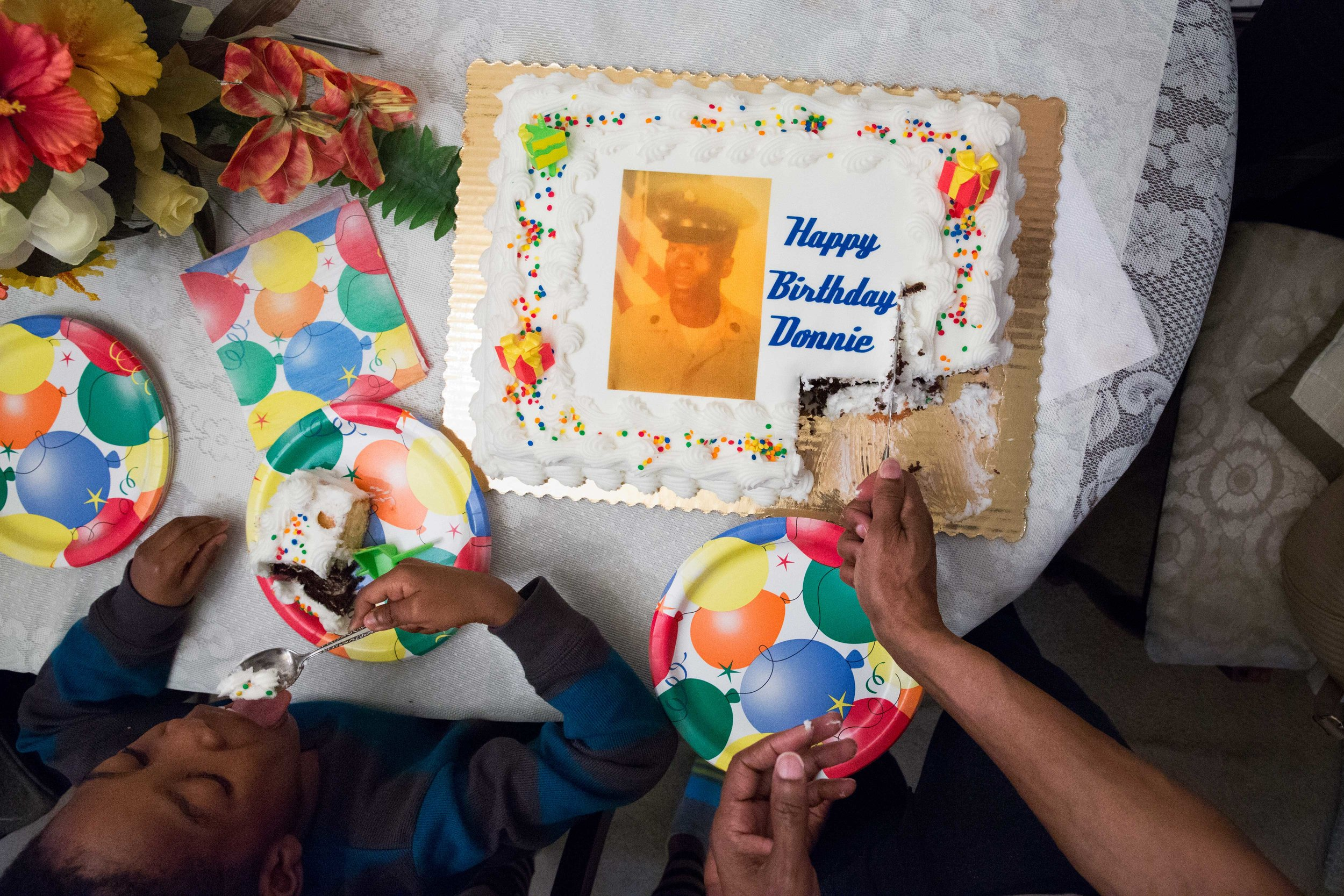 """Ronald, also known as """"Donnie"""" to his family, cuts into his 59th birthday cake with his great-nephew on his left, on January 10, 2016. This birthday marked his first birthday out of prison; the last birthday he remembers as a free man, he was the age of the picture on his cake."""