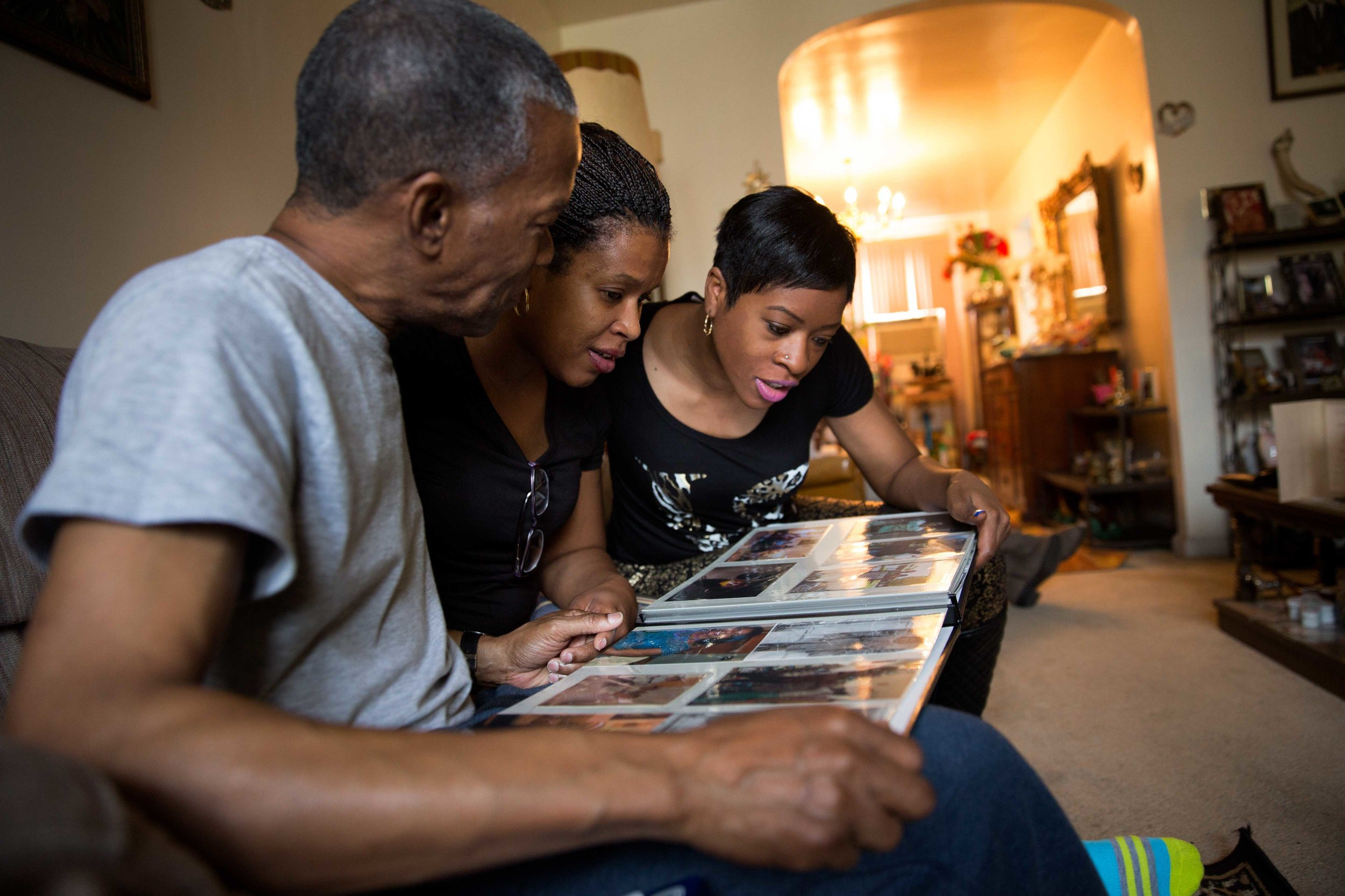 Ronald and his nieces look at a family album at Millie Mae's house.