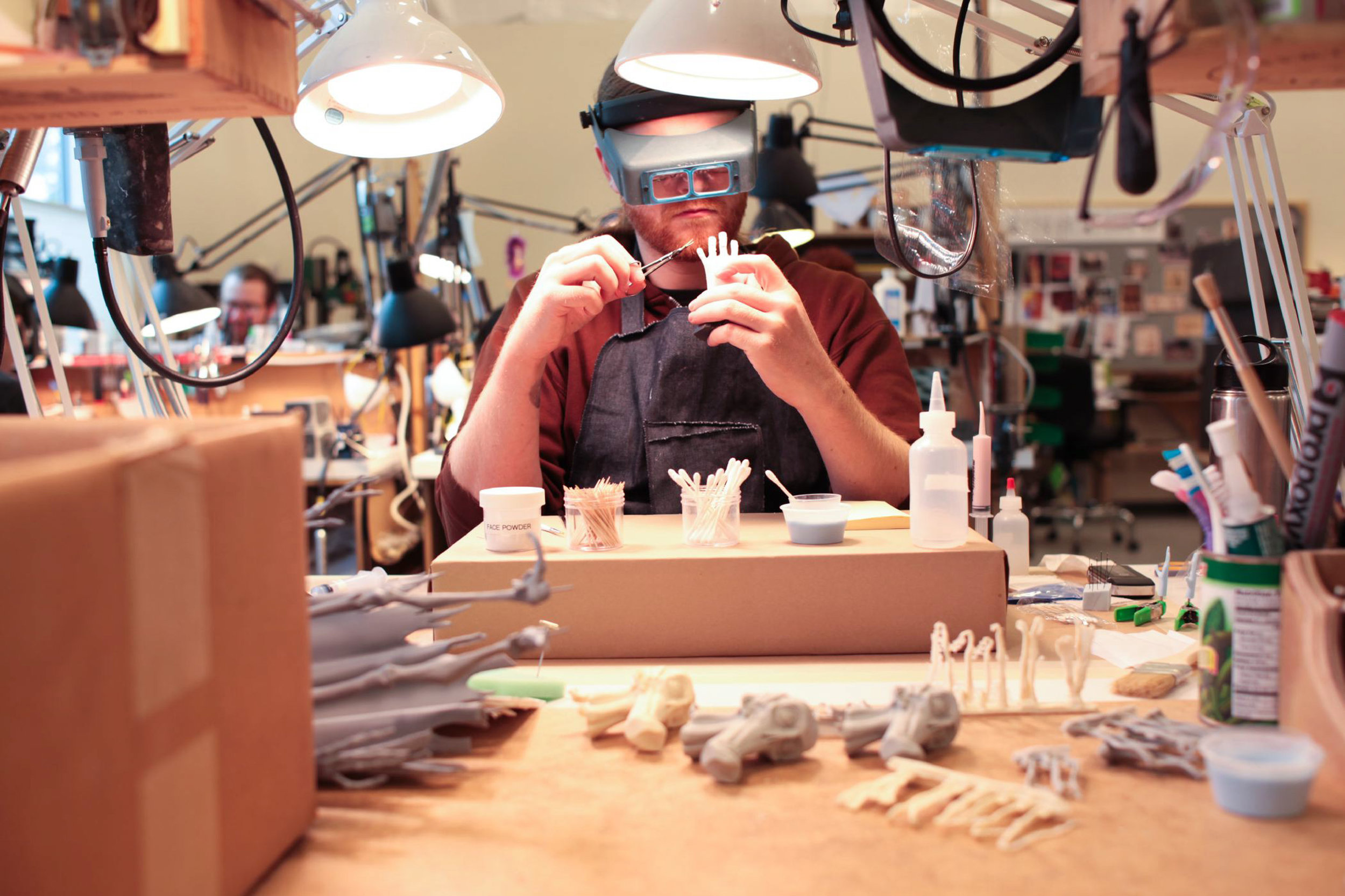 Aaron Matthews carefully paints details on a hand for ParaNorman, the new 3D stop-motion comedy thriller.  Credit: LAIKA, Inc.