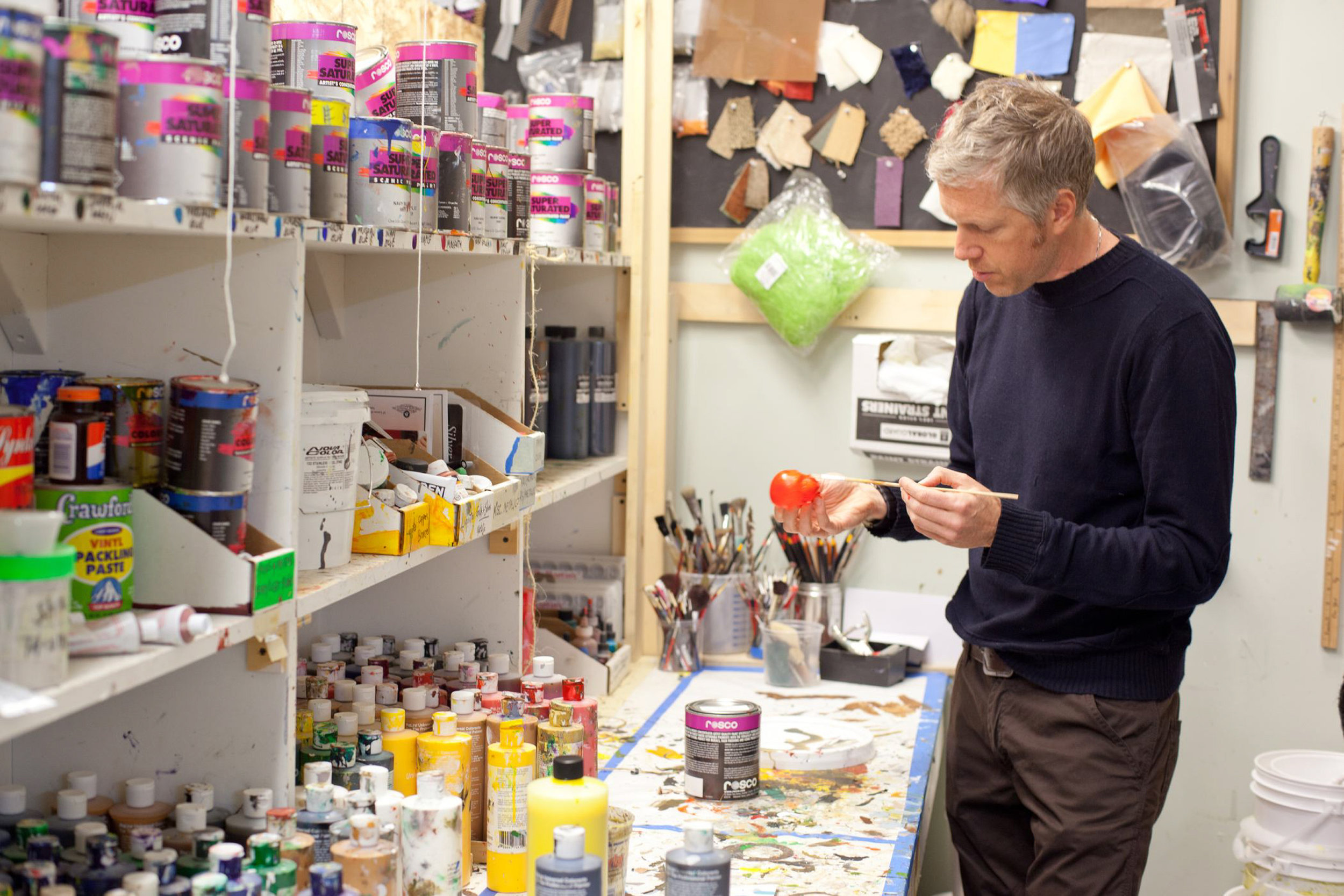 Production Designer Nelson Lowry surveys cans and bottles of paint for ParaNorman, the new 3D stop-motion comedy thriller.  Credit: LAIKA, Inc.