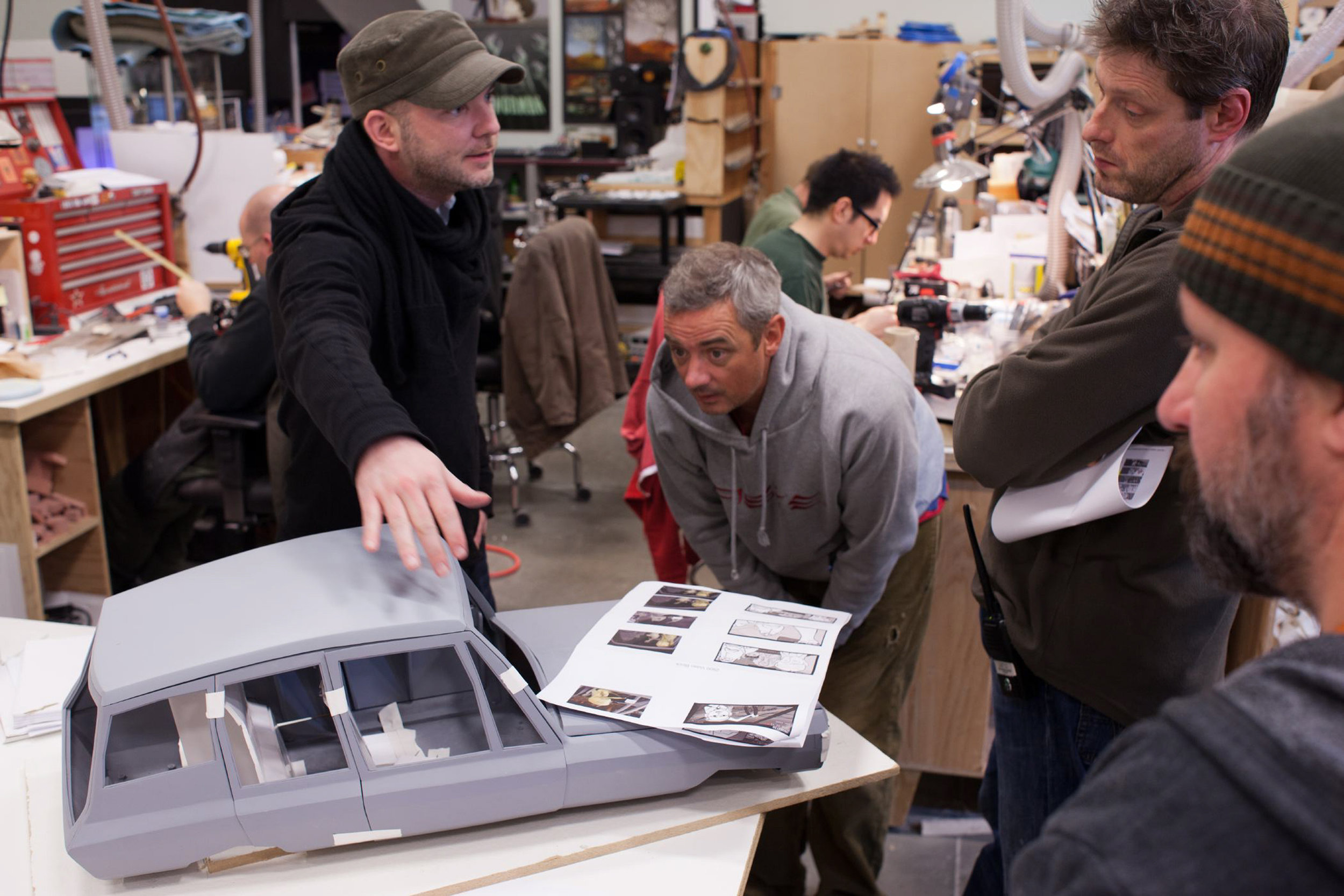 (l to r.) Directors Chris Butler and Sam Fell discuss a car sculpture with Director of Photography Tristan Oliver for ParaNorman, the new 3D stop-motion comedy thriller.  Credit: LAIKA, Inc.