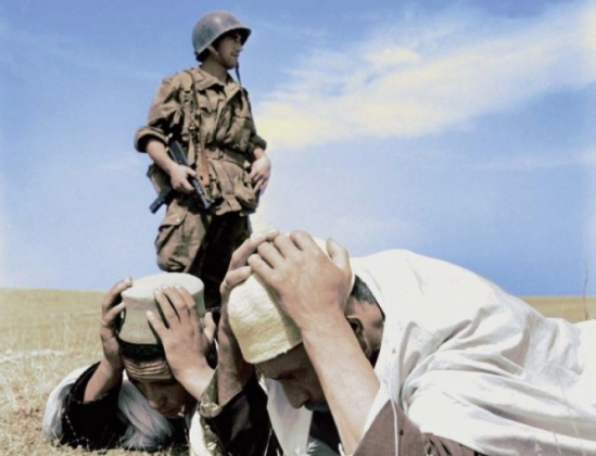 A French soldier arrests two Algerians during the war of 1954-1962