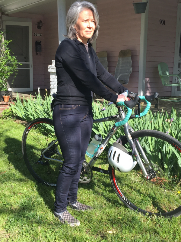 Maria posing with her bike in the Riding Denim in front of the Pink House