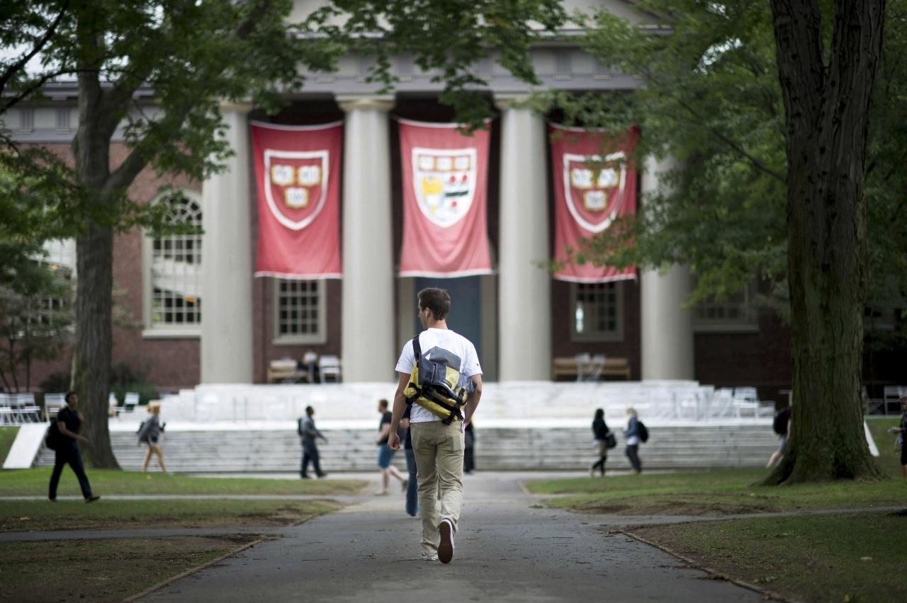 College student walking toward Harvard building