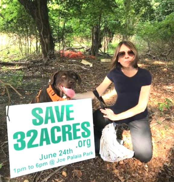 Jacqui with the Save 32 Acre lawn signs that have been posted around the area to raise awareness.