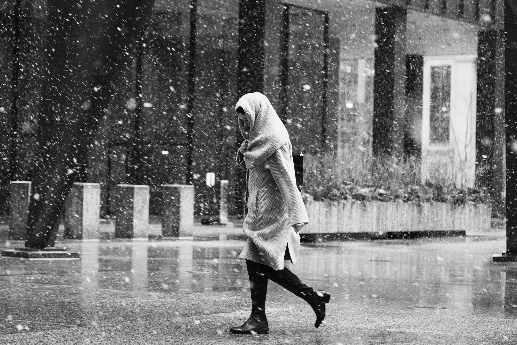 A women covers herself with a scarf while walking pass Chicago's Federal Center on a snowy day, Feb 24, 2016.