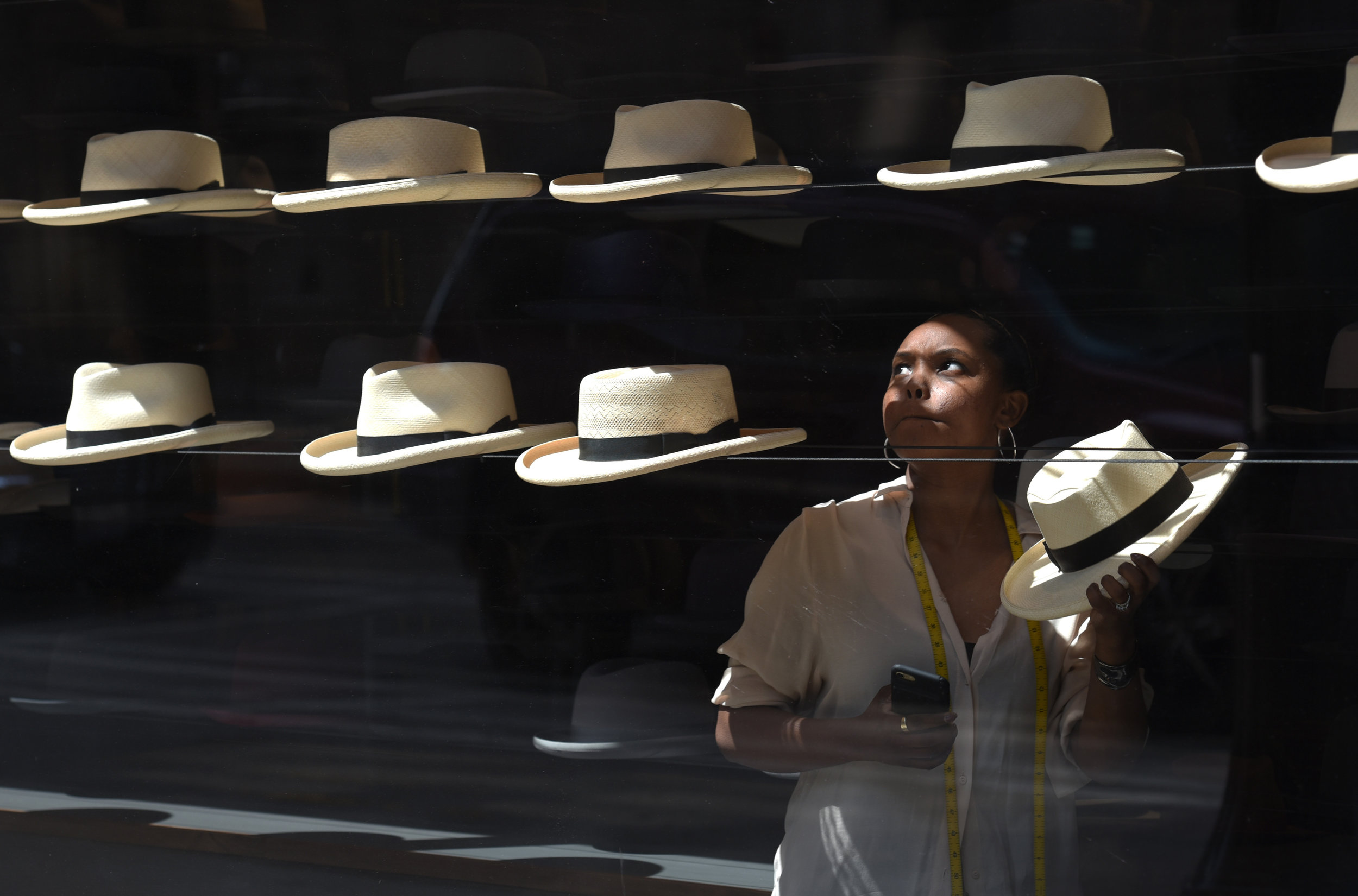 Late morning light illuminates Tiffany Bell as she works at a hat maker shop in downtown Chicago, Friday, July 7, 2017. (AP Photo/G-Jun Yam)
