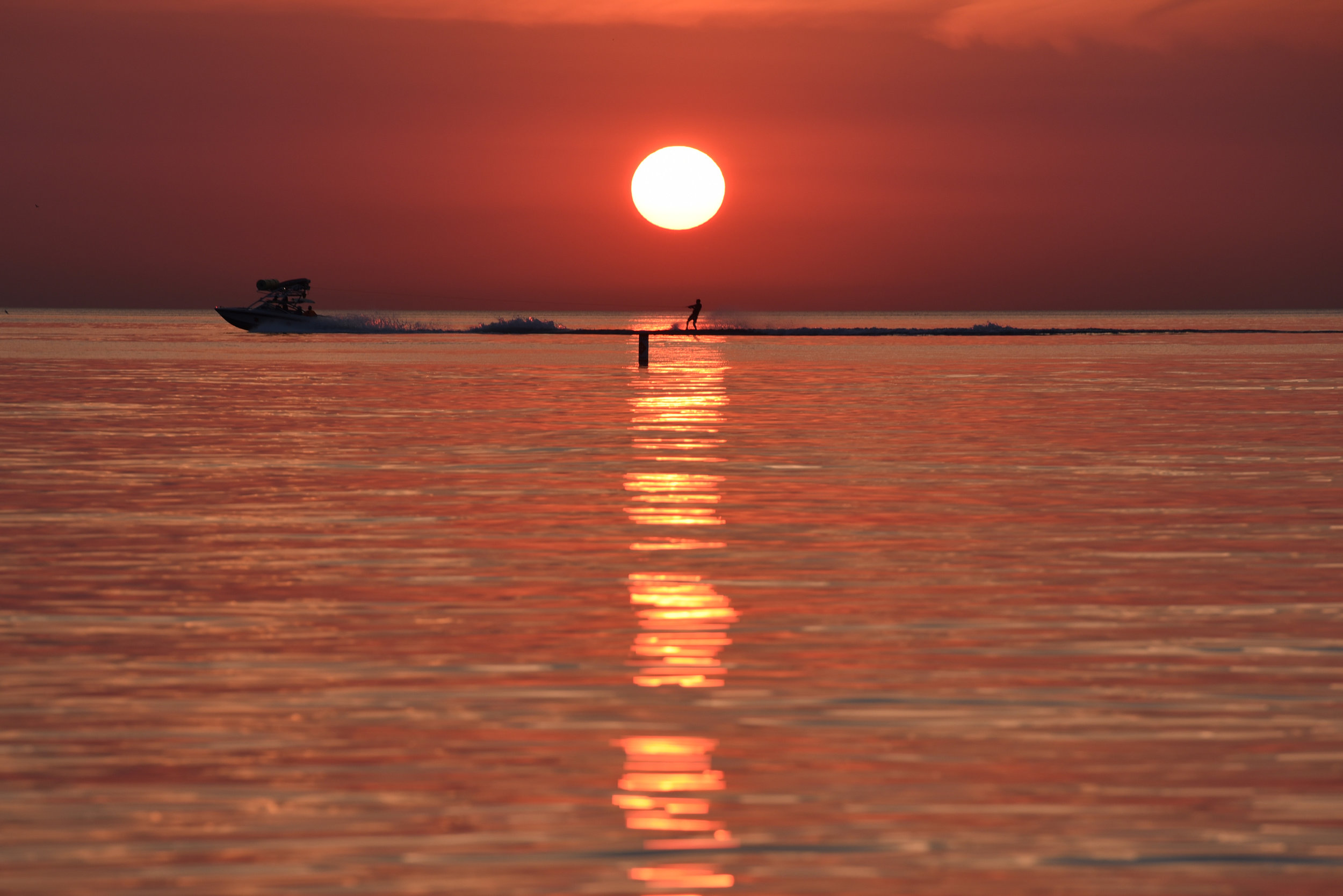 A boat pulls a waterskier through the reflection of the rising sun on Lake Michigan, Tuesday, Aug. 1, 2017 in Chicago. (AP Photo/G-Jun Yam)