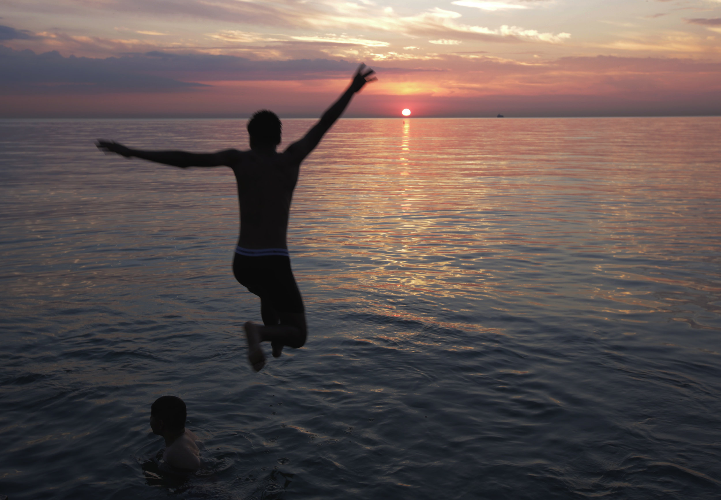 Alex Delgado is silhouetted by the rising sun as he jumps into Lake Michigan, Tuesday, Aug. 1, 2017 in Chicago. (AP Photo/G-Jun Yam)