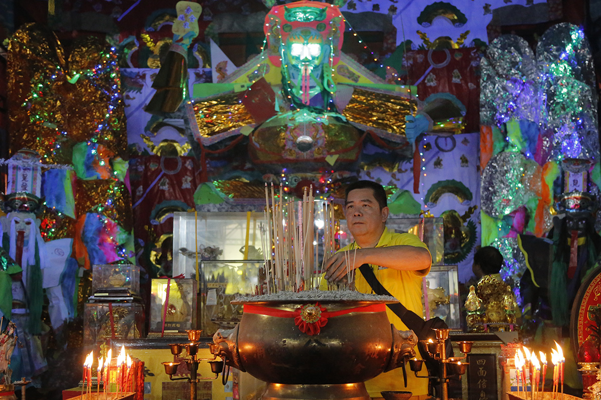 "In this Aug. 16, 2018, photo, a man collects joss sticks in front of a giant paper statue of the Chinese deity ""Da Shi Ye"" or ""Guardian God of Ghosts"" during the Chinese Hungry Ghost Festival in Puchong, Malaysia. (AP Photo/Yam G-Jun)"