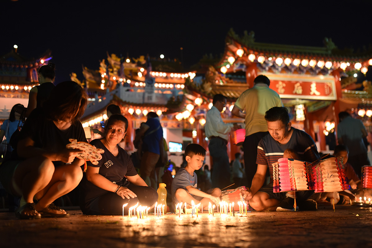 Ethnic Chinese people light candles as they celebrate Mid-Autumn Festival at a temple in Kuala Lumpur, Malaysia, Monday, Sept. 24, 2018. (AP Photo/Yam G-Jun)
