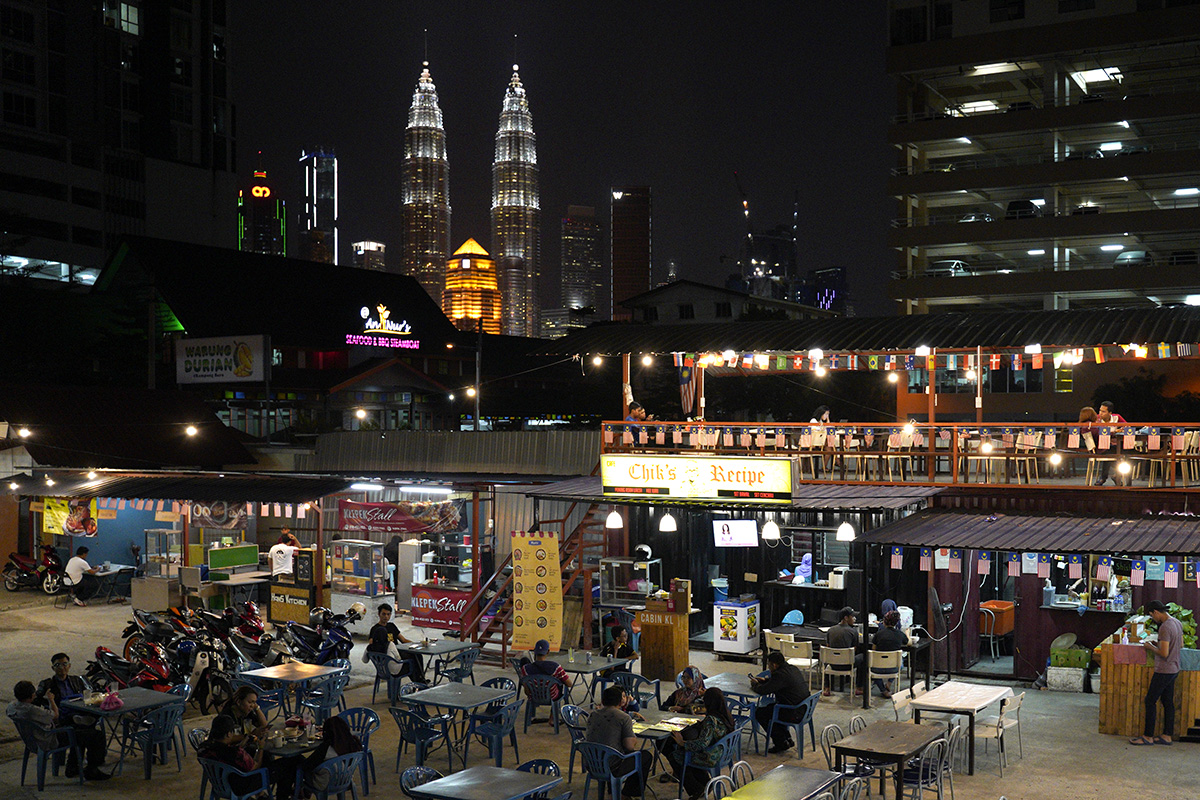 In this Thursday, Nov. 1, 2018, photo, Malaysia landmark building Petronas Twin Towers stands behind a cafe in Kampung Baru, Malaysia. (AP Photo/Yam G-Jun)