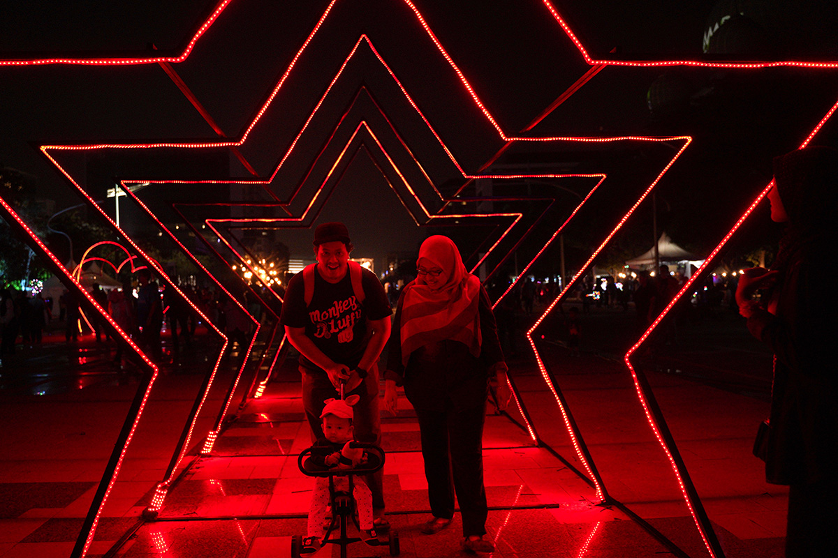 Festival goers walk through a light installation during the Light And Motion Putrajaya 2018 event in Putrajaya, Malaysia, Sunday, Dec. 30, 2018.(AP Photo/Yam G-Jun)