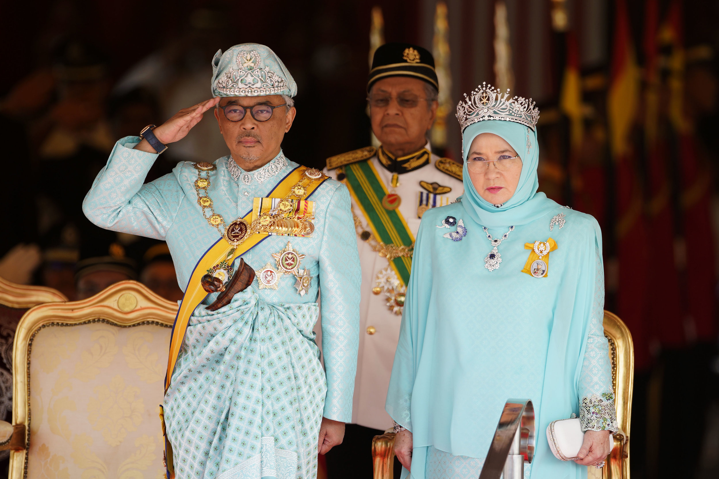 Malaysia's King Sultan Abdullah Sultan Ahmad Shah salutes next to Queen Tunku Azizah Aminah Maimunah and Prime Minister Mahathir Mohamad, center, during his welcome ceremony at Parliament House in Kuala Lumpur, Malaysia, Thursday, Jan. 31, 2019. (AP Photo/Yam G-Jun)