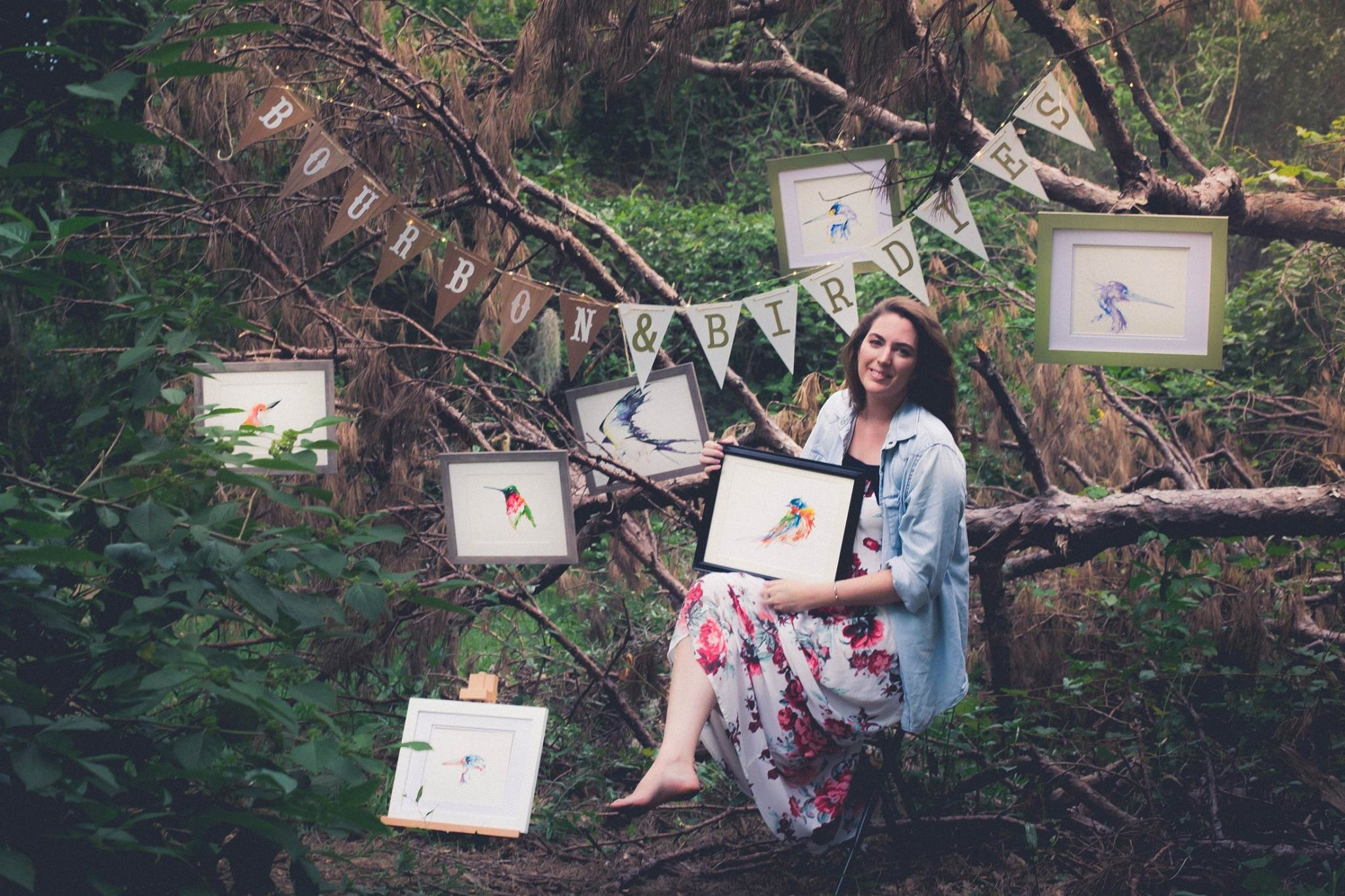 Florida watercolor artist Kristen Summers in a forest gallery surrounded by her birds