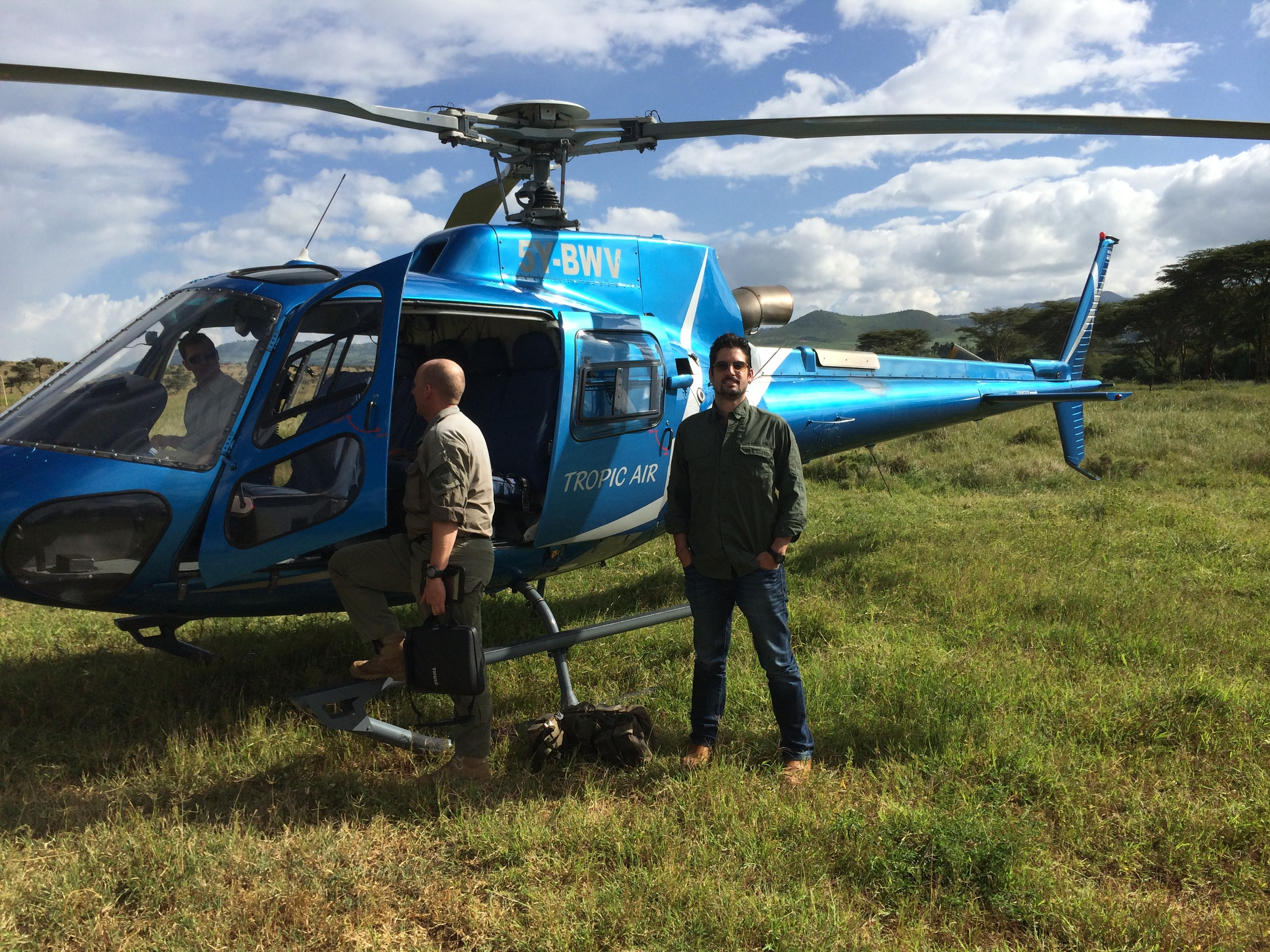 Me next to our helicopter just before flying over Kenya.JPG
