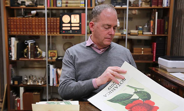 Brad Parberry, founder of Cavallini & Co., flipping through one of his calendars with vintage botanical prints