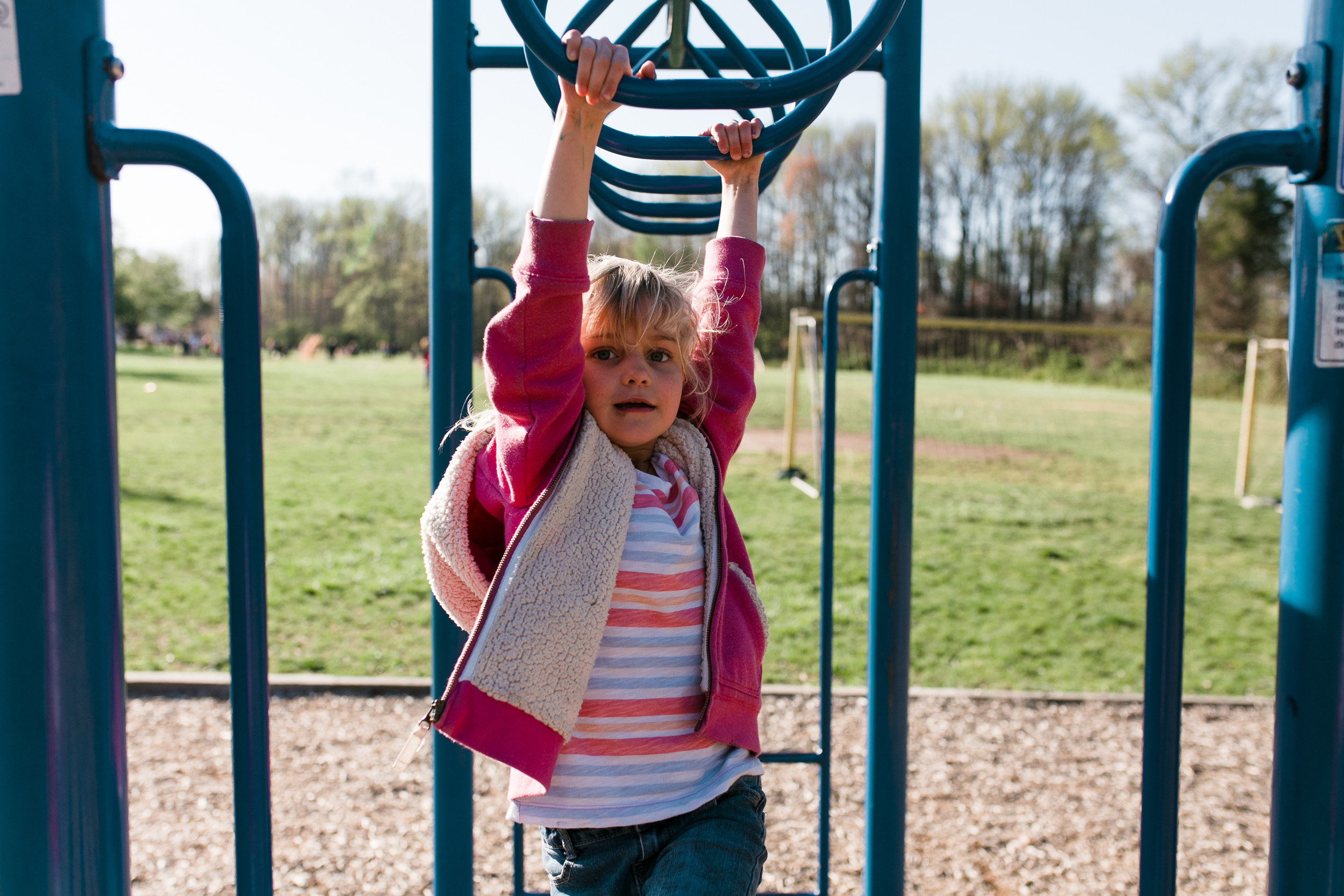 a girl swings on some monkey bars in annapolis MD | children and family photography